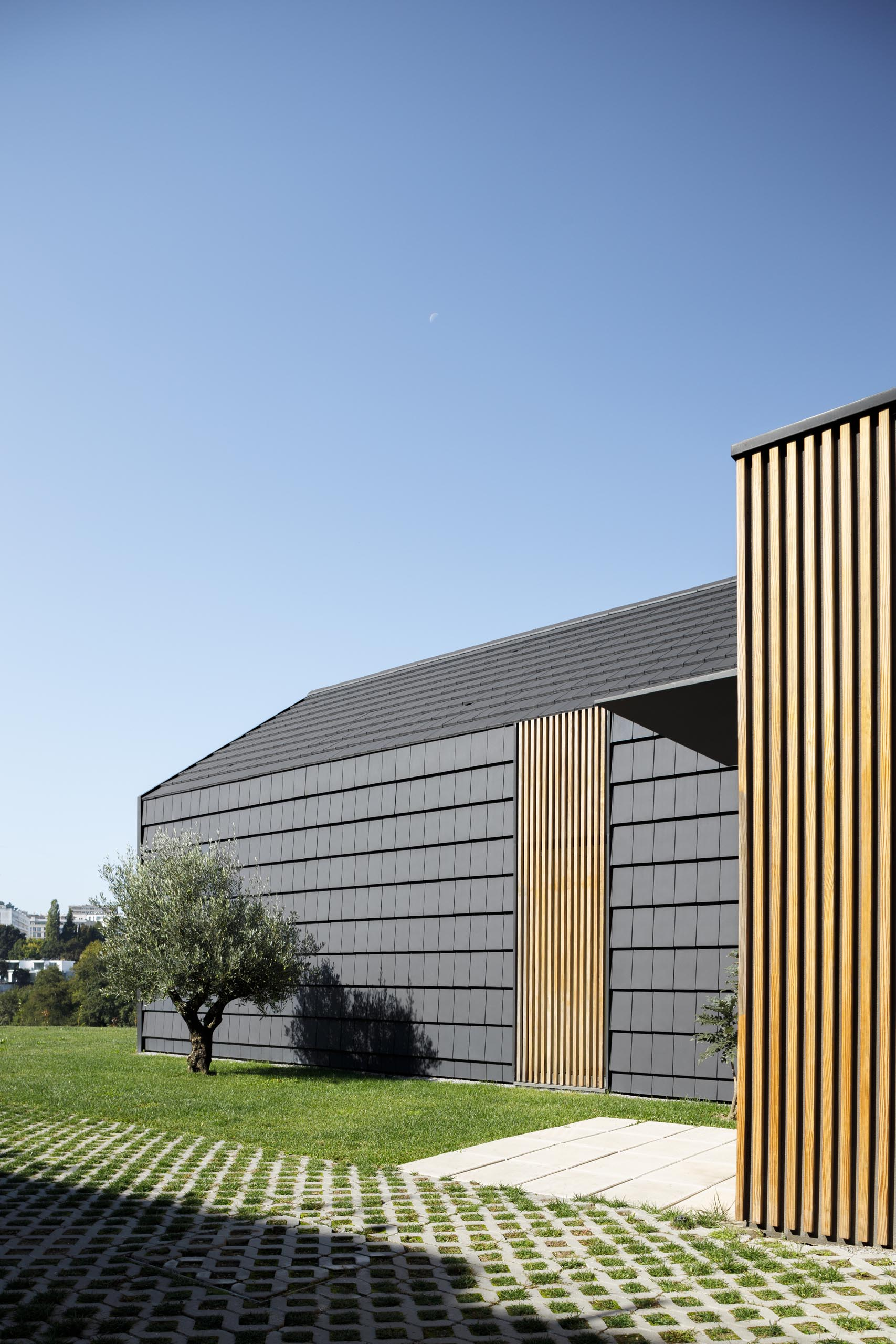A modern home with black shingle exterior and wood slat accents.