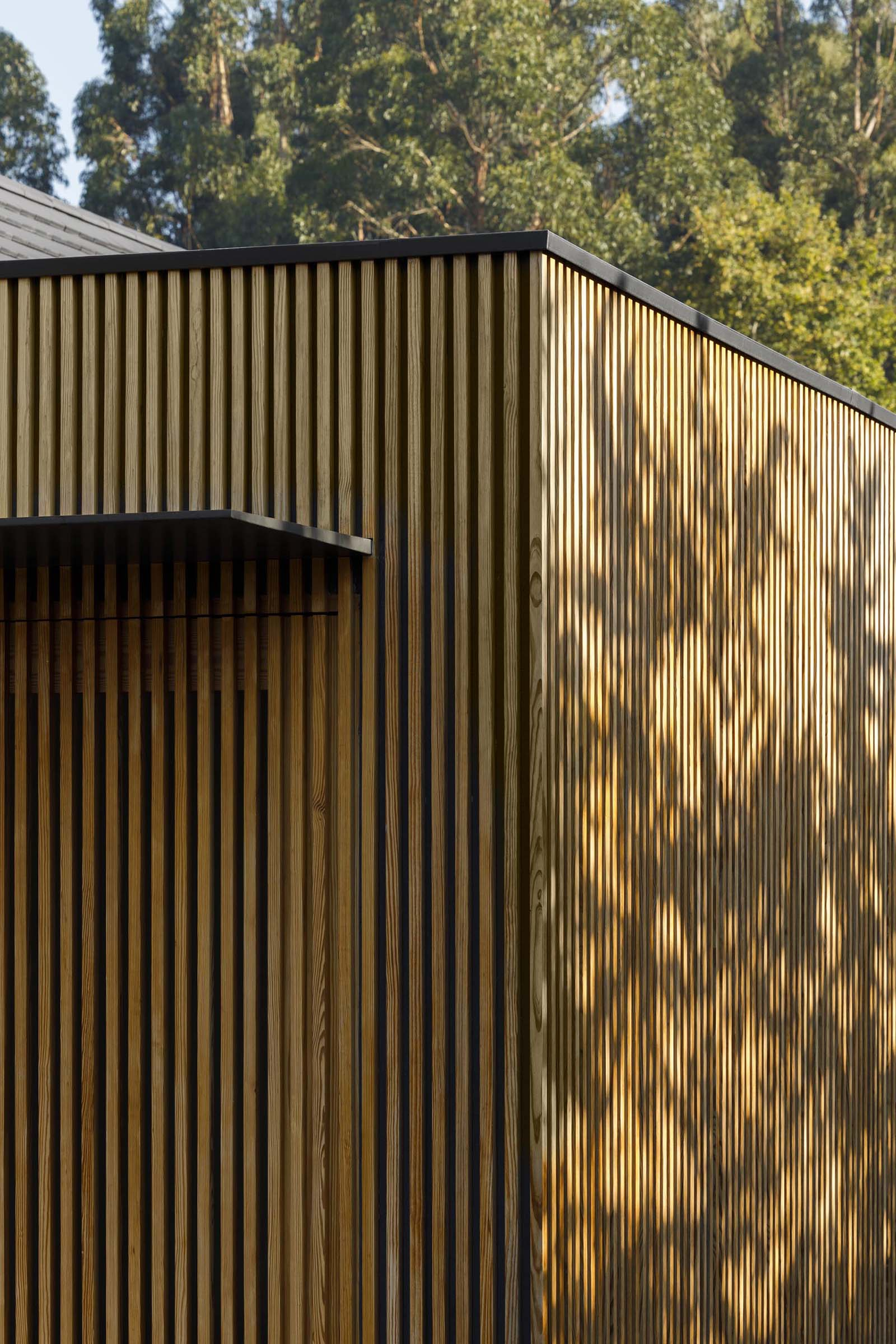 A modern house with a wood slat exterior and an integrated door.