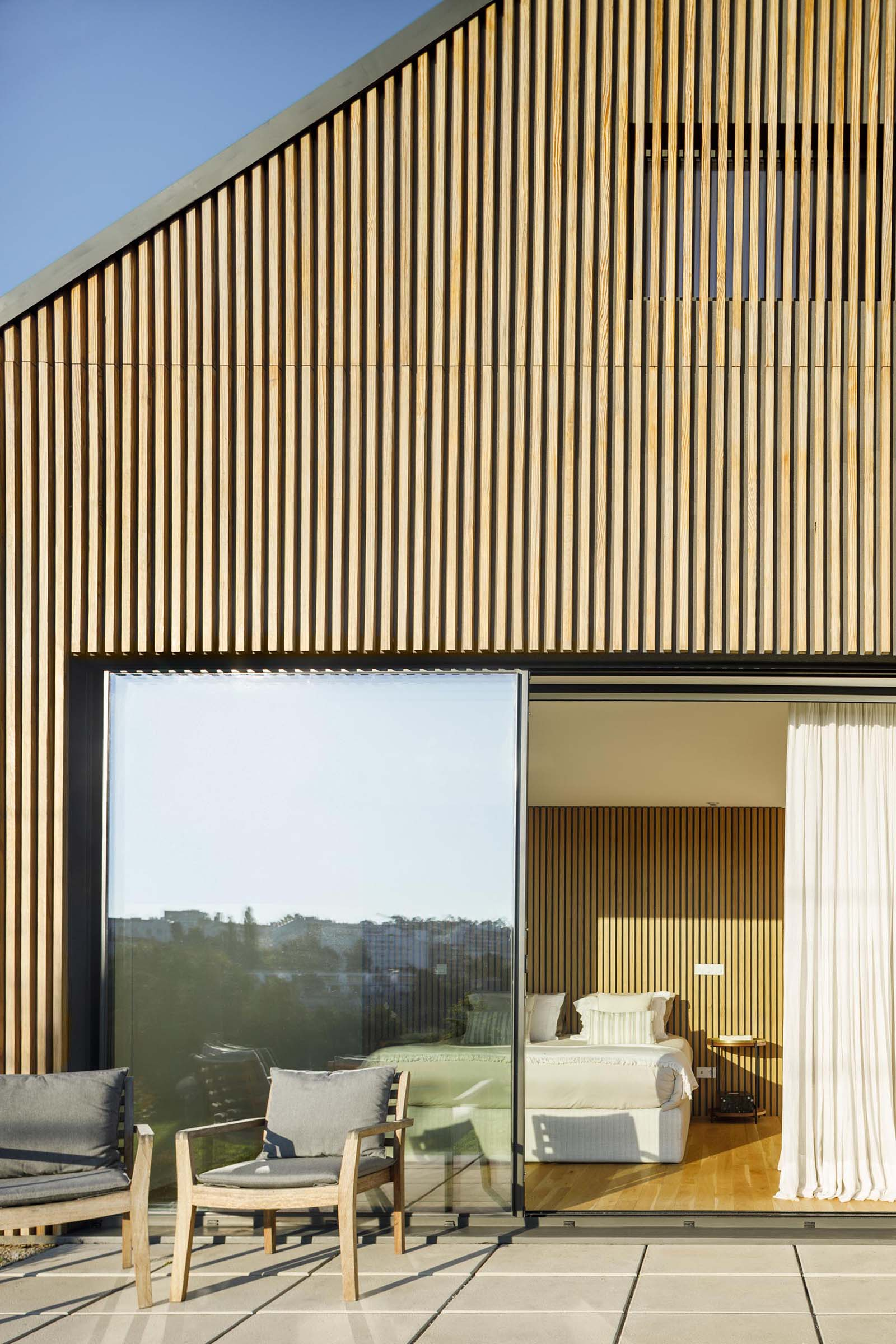 A modern house with a wood slat exterior and large sliding glass doors.