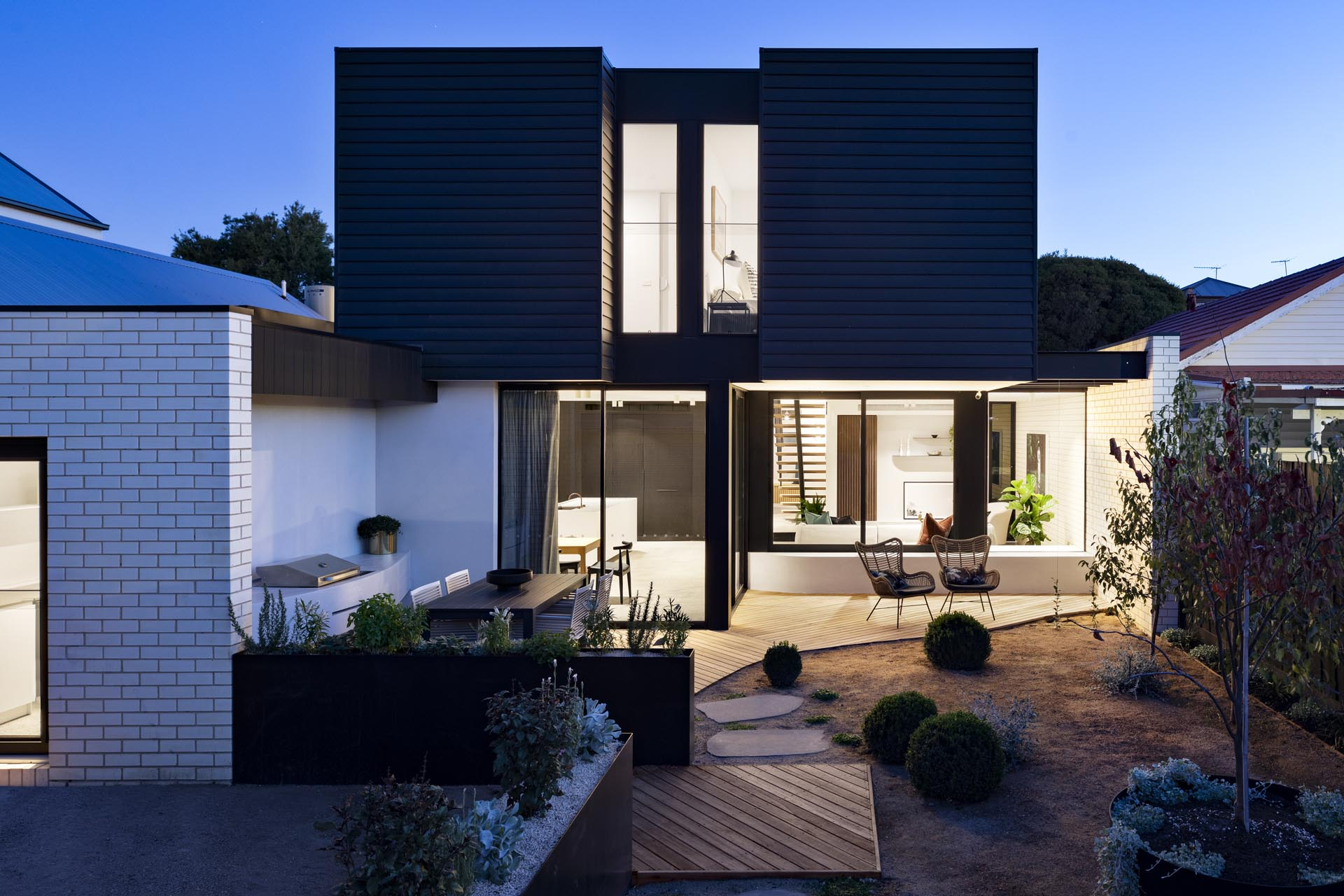 A modern house extension that has a black facade, a landscaped yard with a bbq, outdoor dining area, and patio.