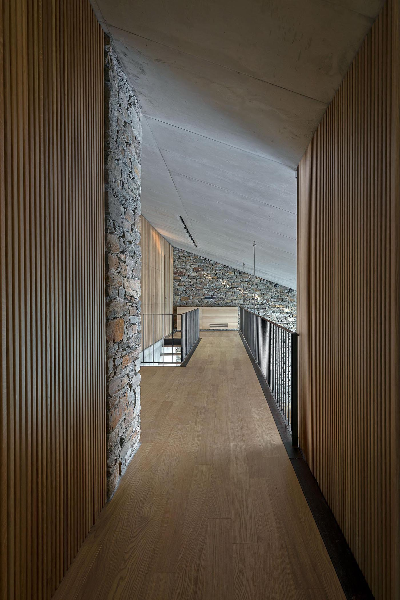 A modern home with stone walls and an interior bridge.