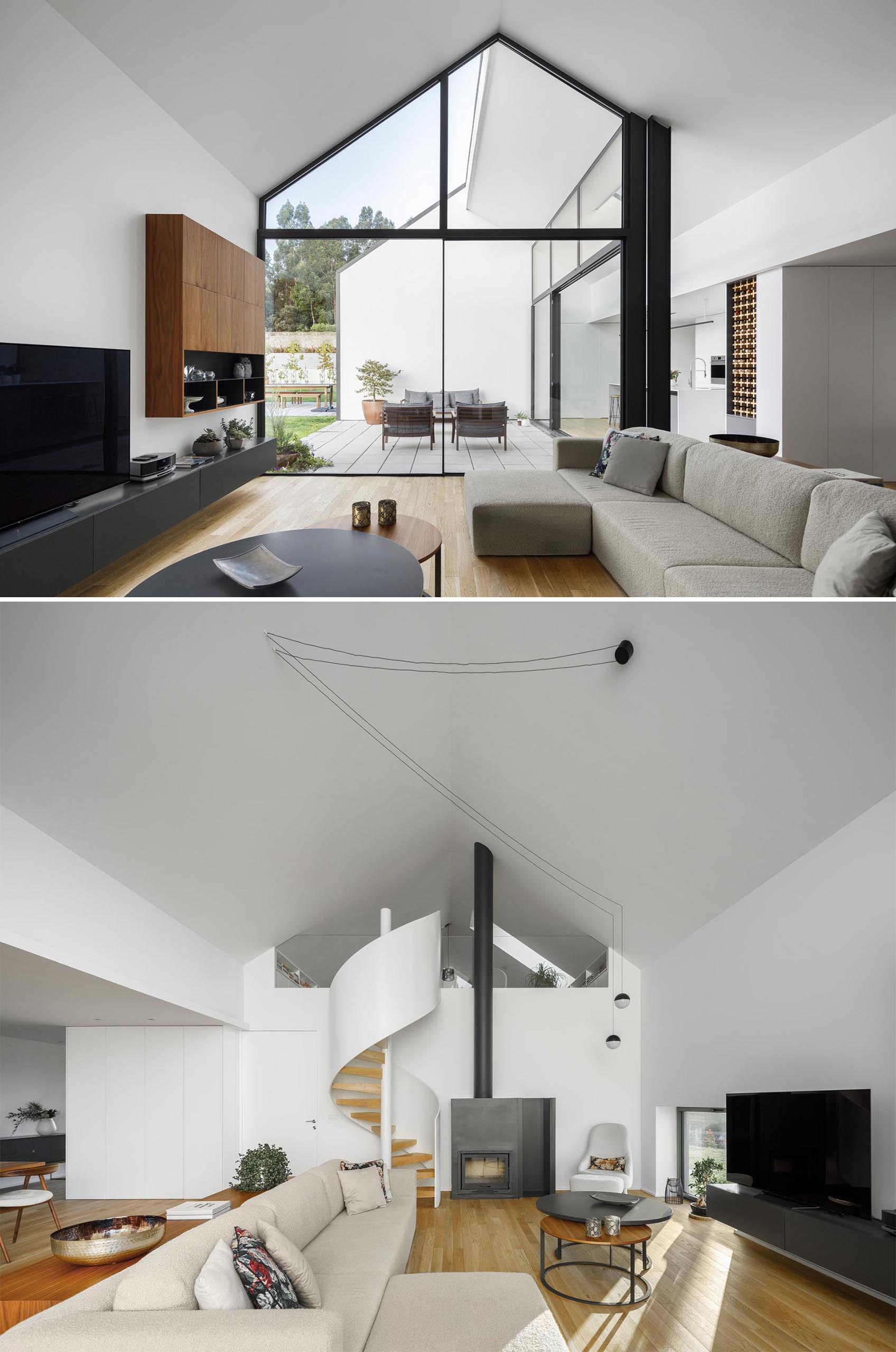 A modern living room with a gabled ceiling, white spiral staircase, and fireplace with a black steel surround.
