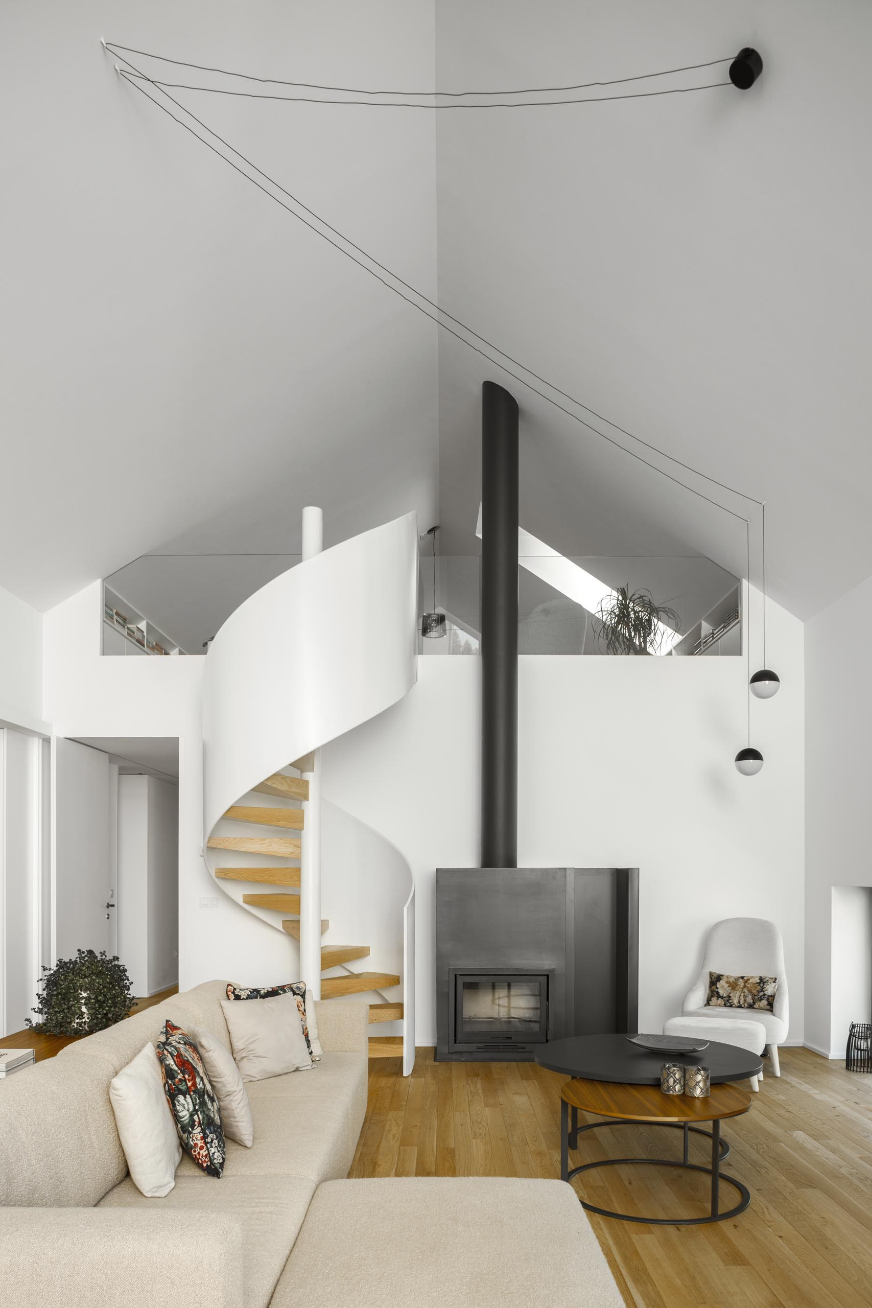 Modern white and wood spiral stairs and a fireplace with a black steel surround.