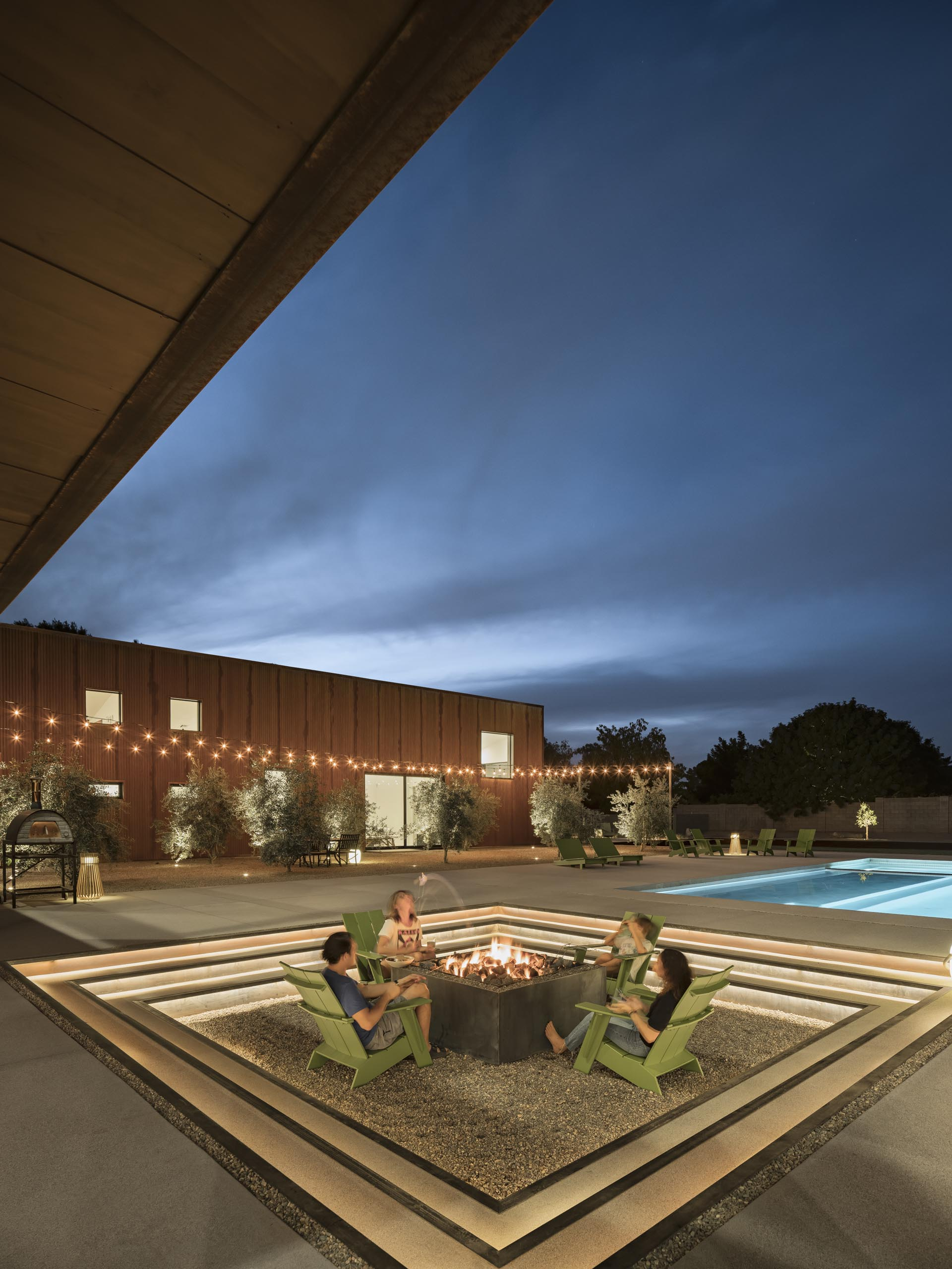 At night, the steps of this modern sunken fire pit are highlighted with hidden lighting, making the perfect place to relax on a cool evening.