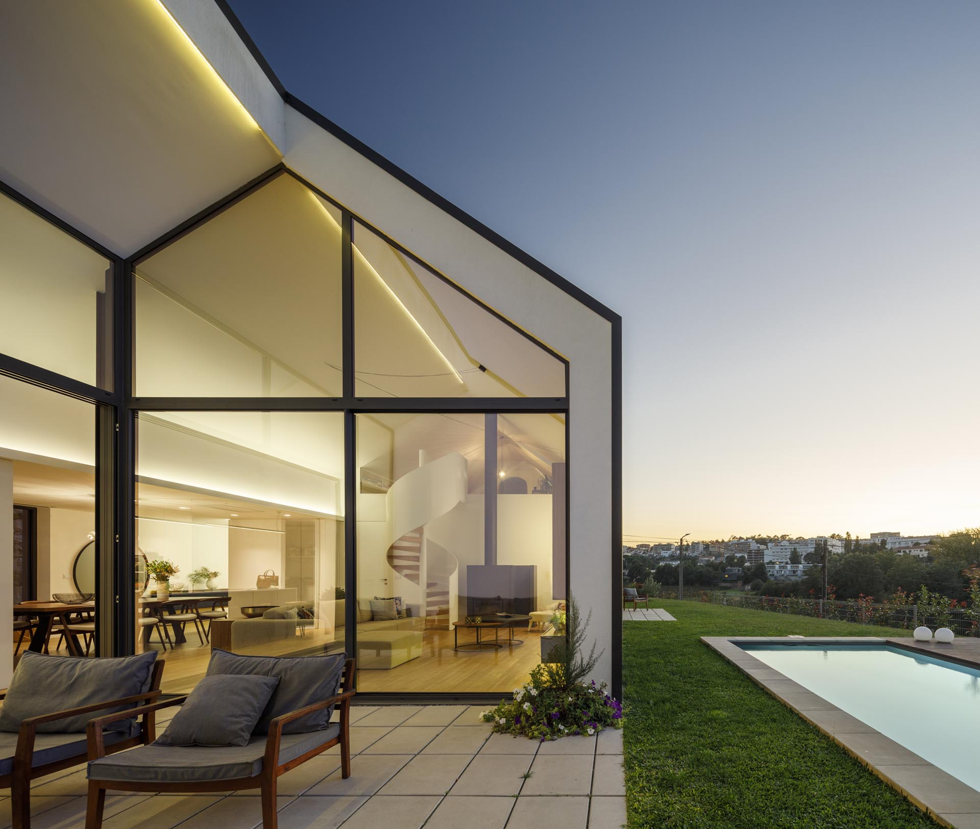 A modern house open to a small patio, the yard, and a swimming pool.