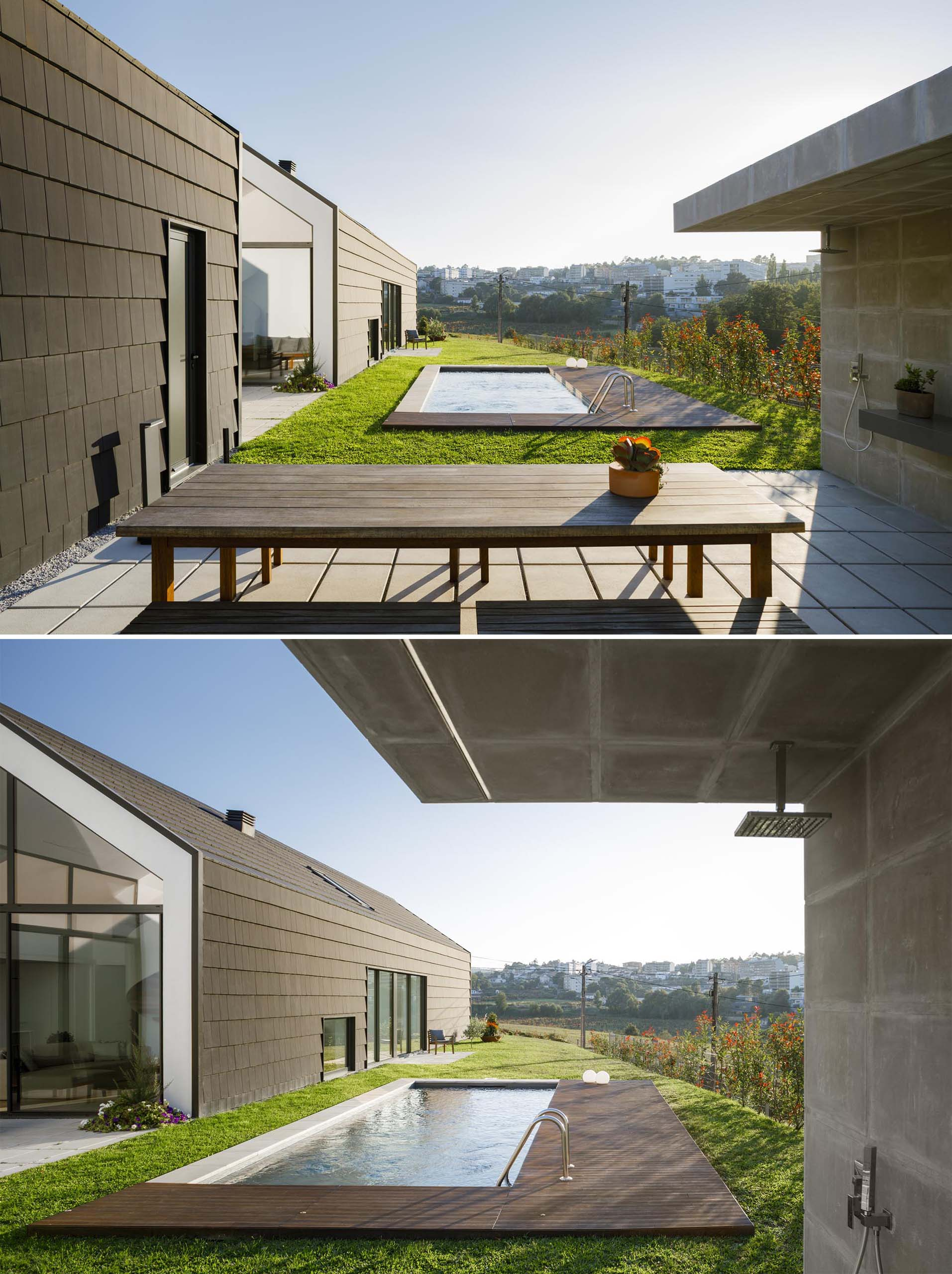 A modern swimming pool with a partial wood deck and an outdoor shower.