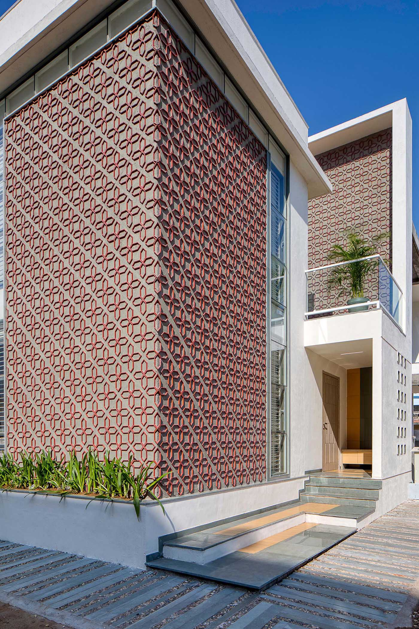 A modern house design with a unique patterned accent wall on its facade.