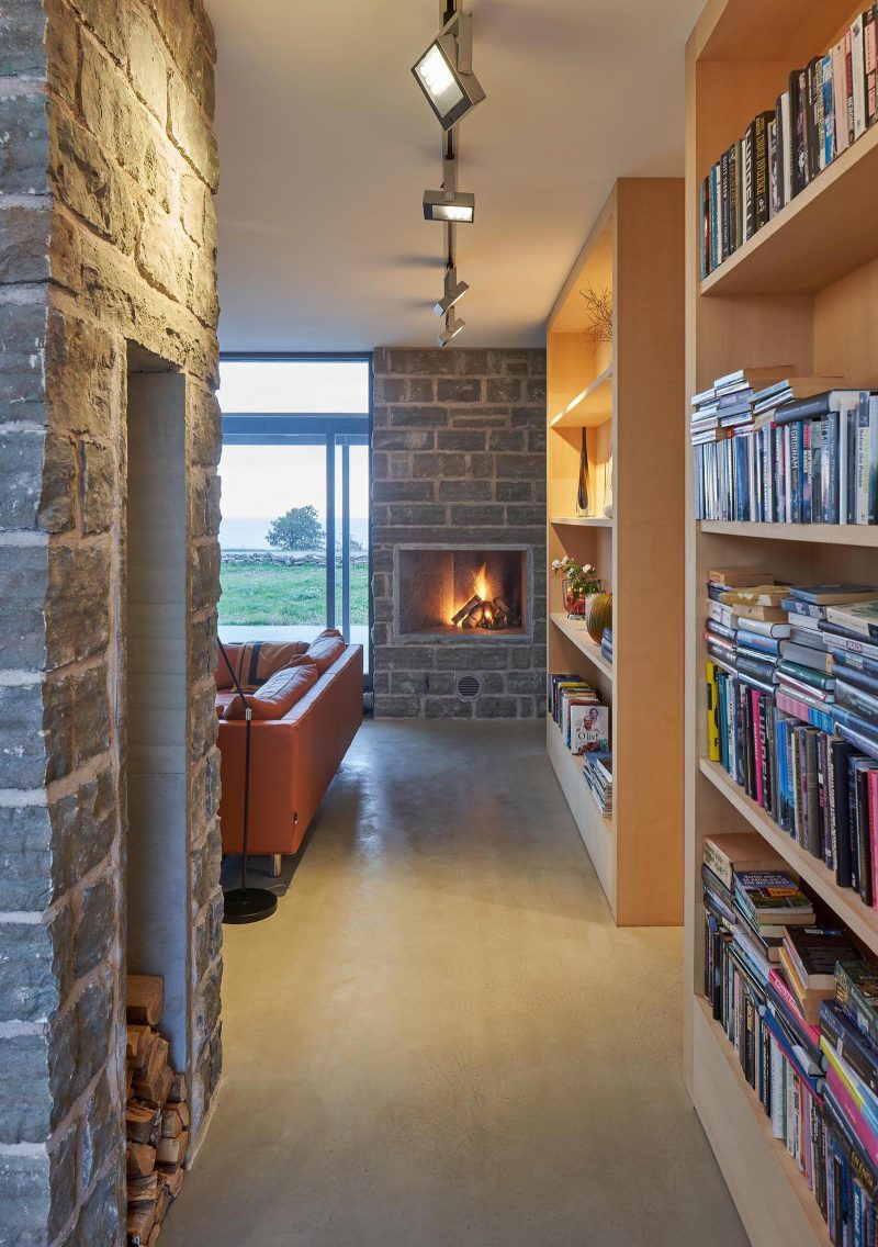 A contemporary summer home with limestone walls, concrete floors, and wood bookshelves.