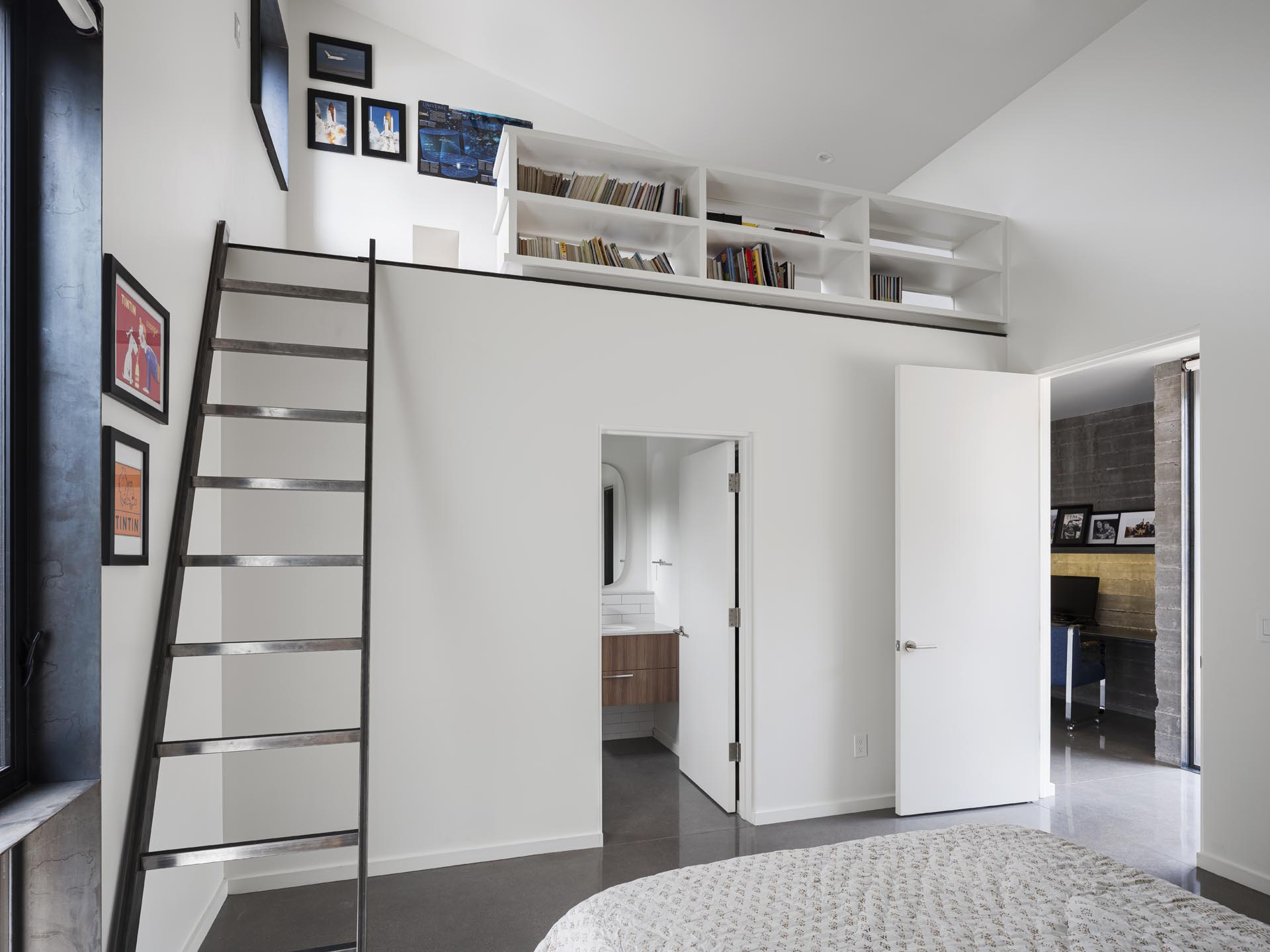 In this modern bedroom, there's a lofted reading area and an en-suite bathroom.