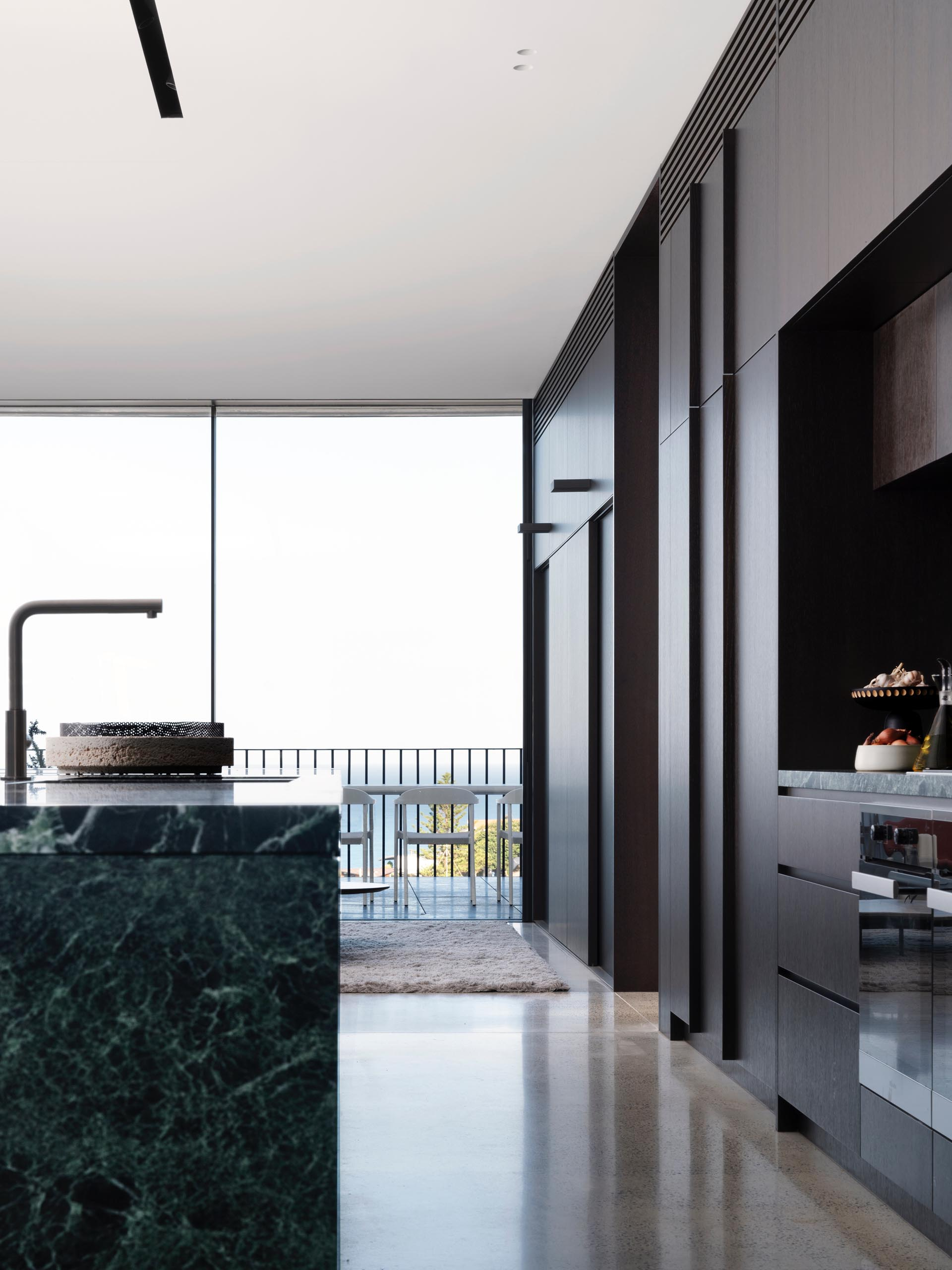 In this modern kitchen, dark wood cabinets complement the gray/black feature marble used on the island and backsplash.