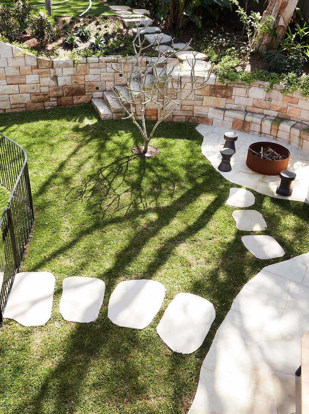 A sandstone wall incorporates seating around a fire pit, and includes steps that lead up to an upper level of the garden.
