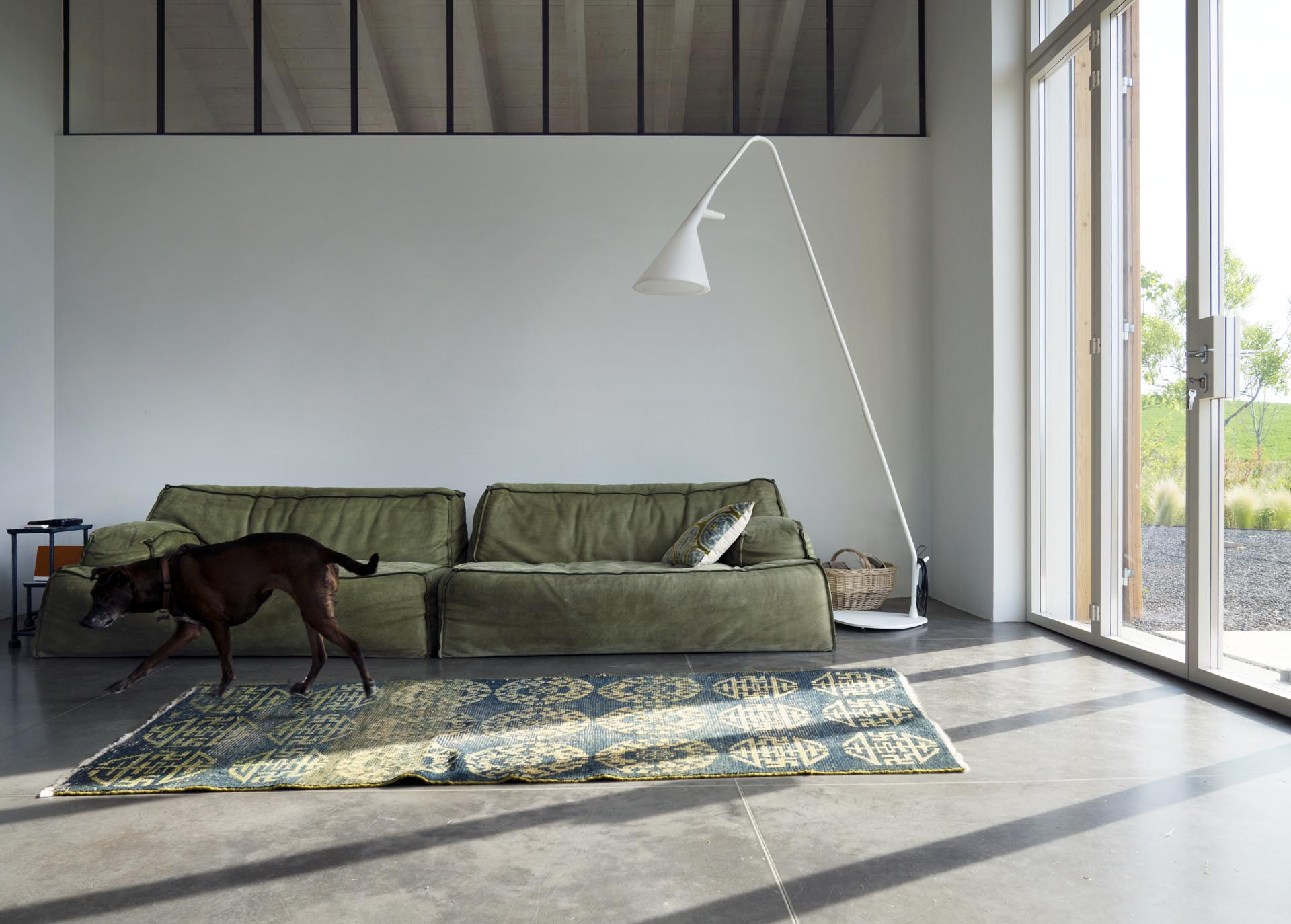 A modern farmhouse living room with white lime tempera walls and concrete floors.