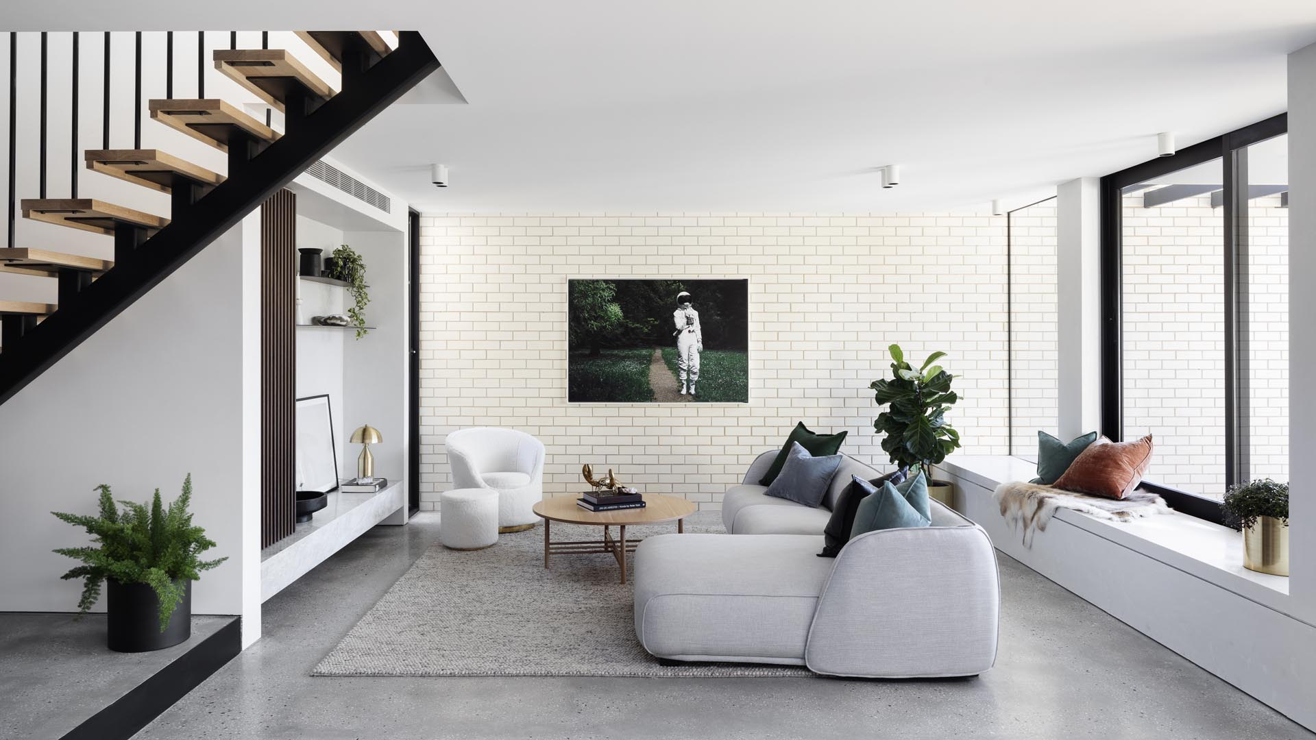 A modern white living room with a brick accent wall and built-in window bench.