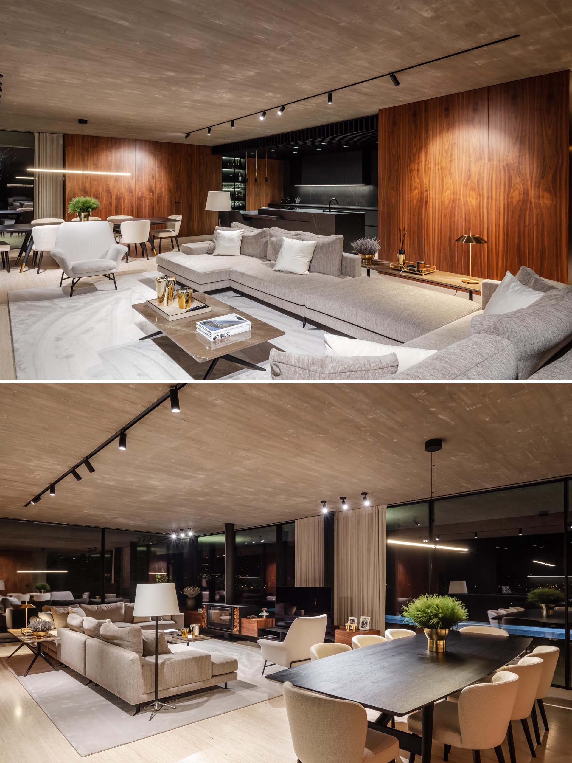 At night, the  interior lighting in this modern home showcases the wood wall accents and other design elements, like the television and fireplace.