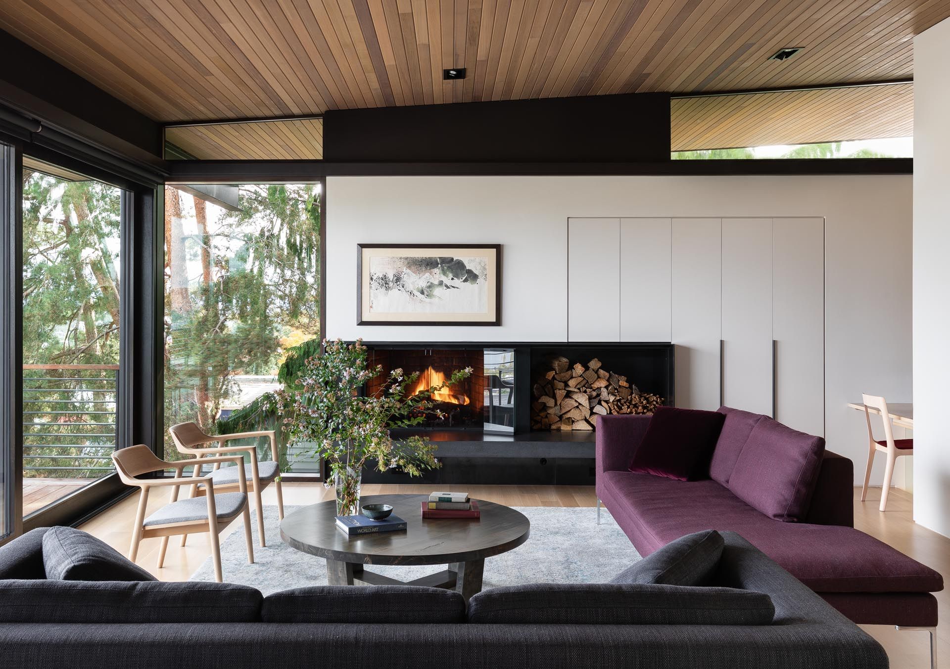 In this modern living room there's a fireplace and clerestory windows.