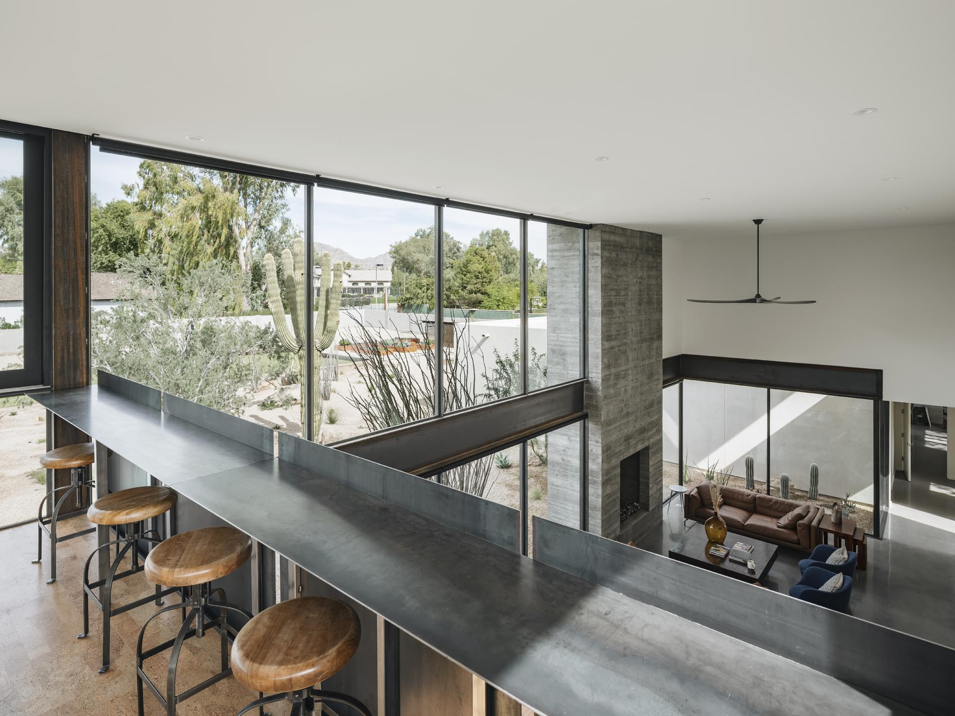 A lofted area has a steel bar for taking in the views of the lower level and distant mountain views.