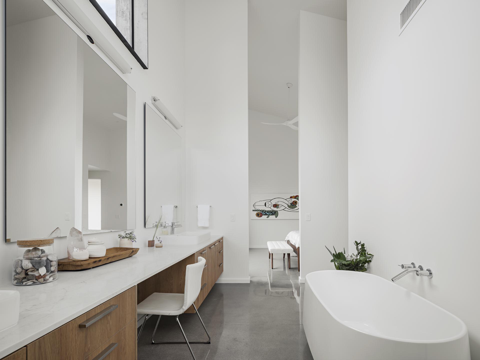 A modern en-suite bathroom has a long vanity as well as a freestanding bathtub.
