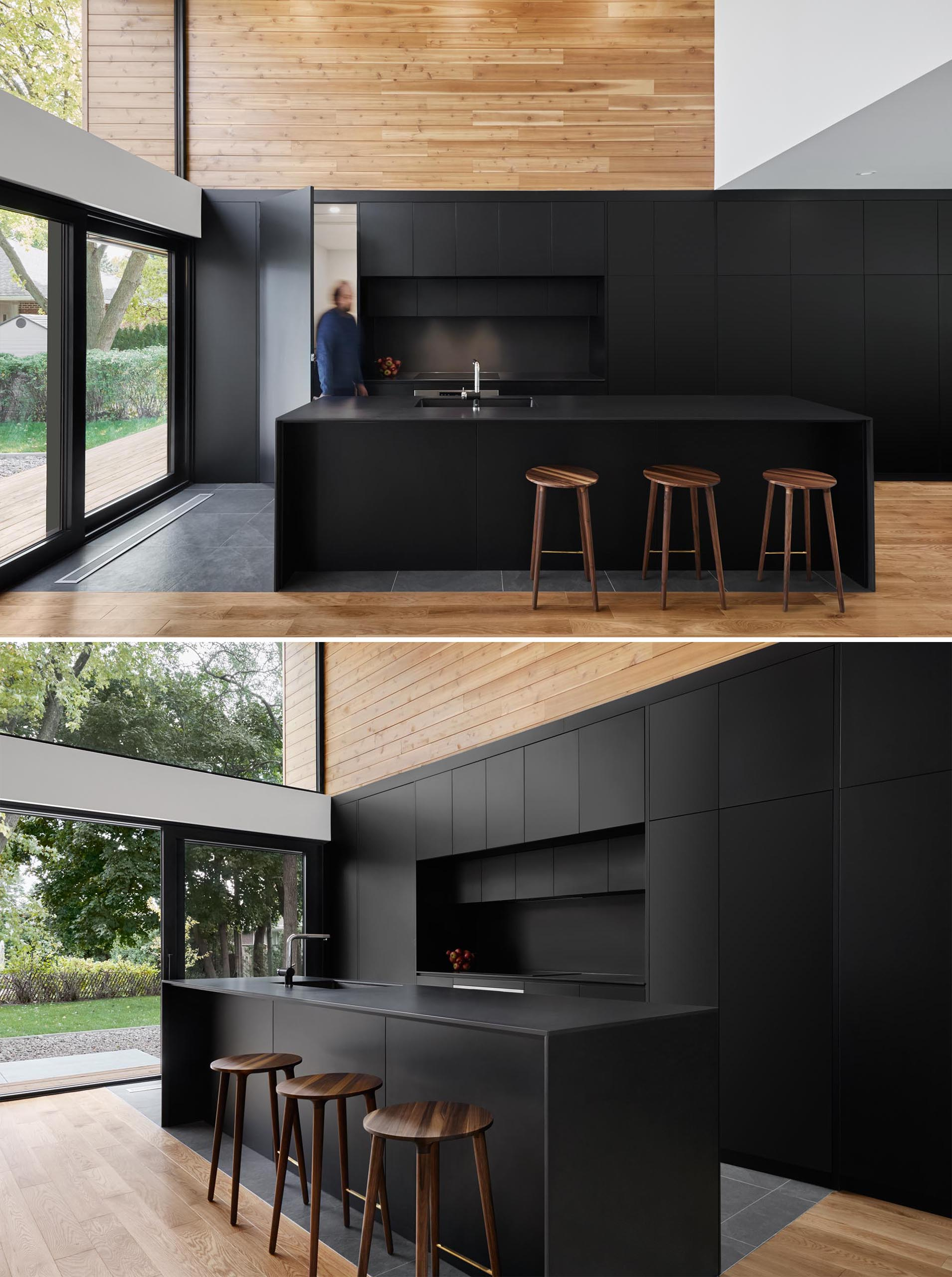 A modern matte black kitchen with integrated appliances and black countertops.