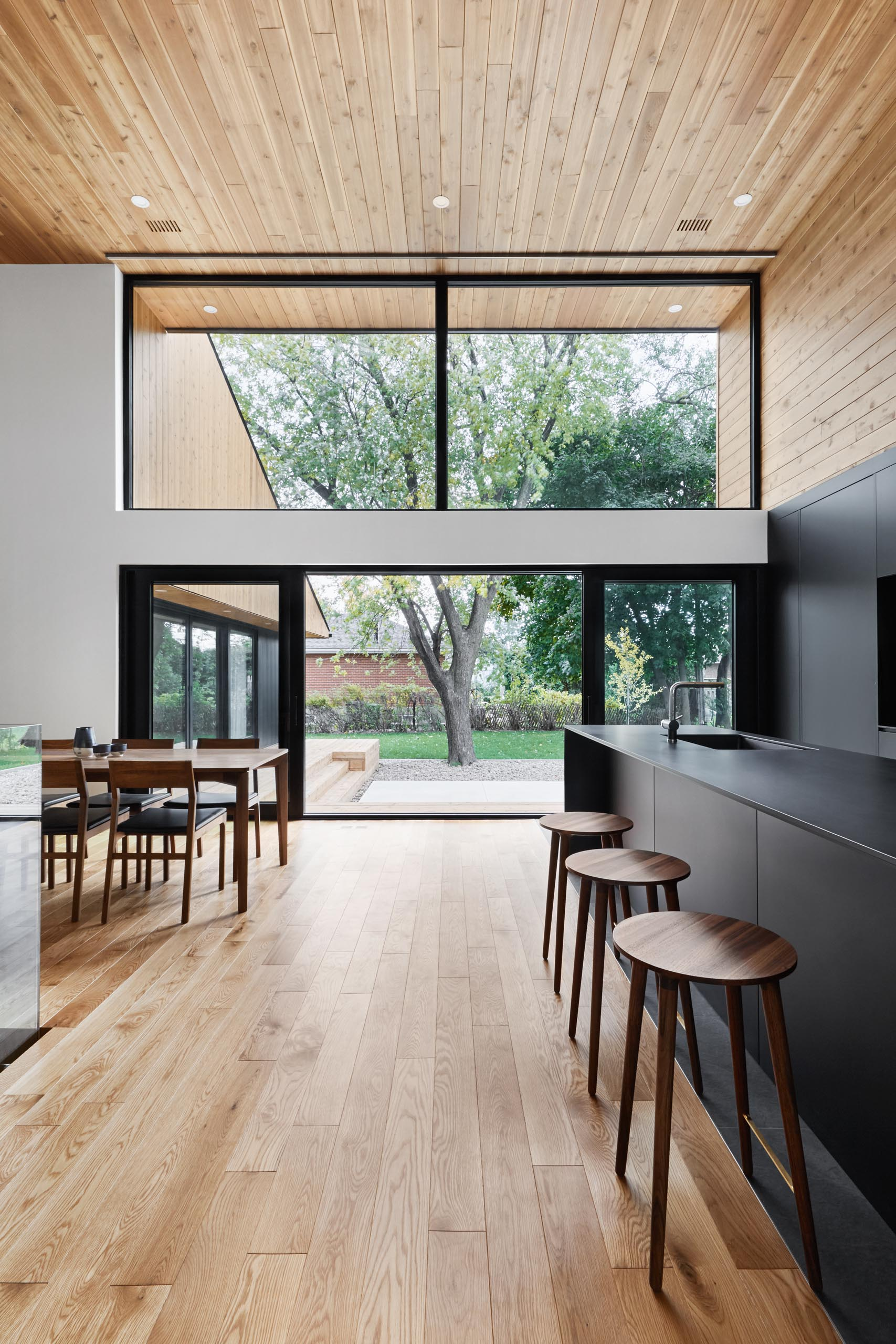 A modern home with high wood ceilings, large windows, a matte black kitchen, and open plan interior.
