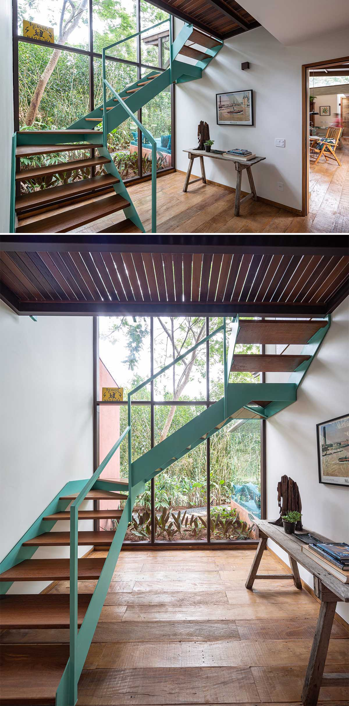 A staircase with a light turquoise blue frame and wood treads connects the two levels of the home.
