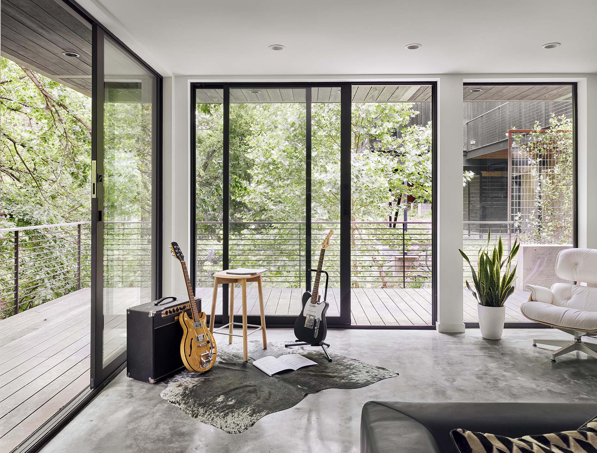 A modern living room with floor-to-ceiling windows and sliding glass doors.