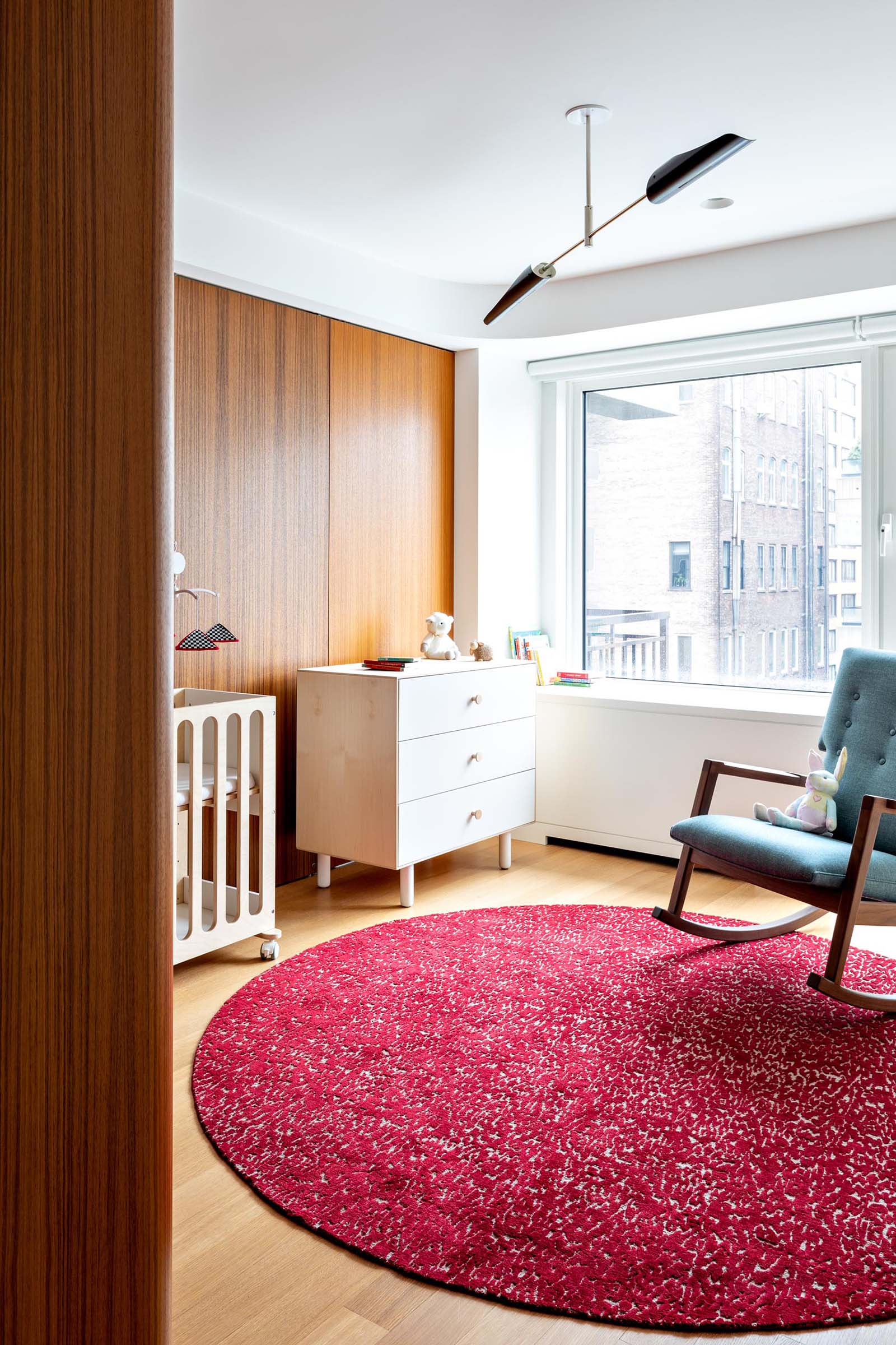 A modern nursery room with a colorful pink rug and a blue rocking chair.