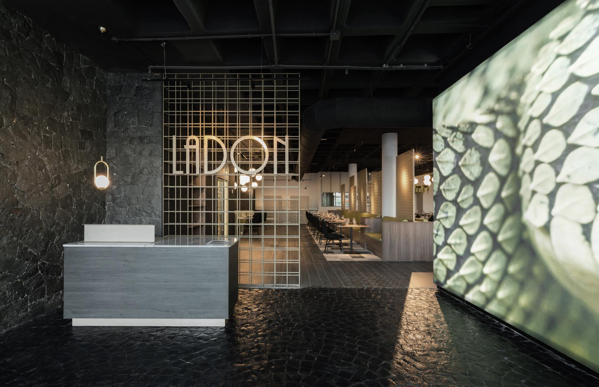 A restaurant lobby inspired by dragons with Volcanic stone walls and floors, copper structures, black ceramic scales and a large image of a dragon's skin.