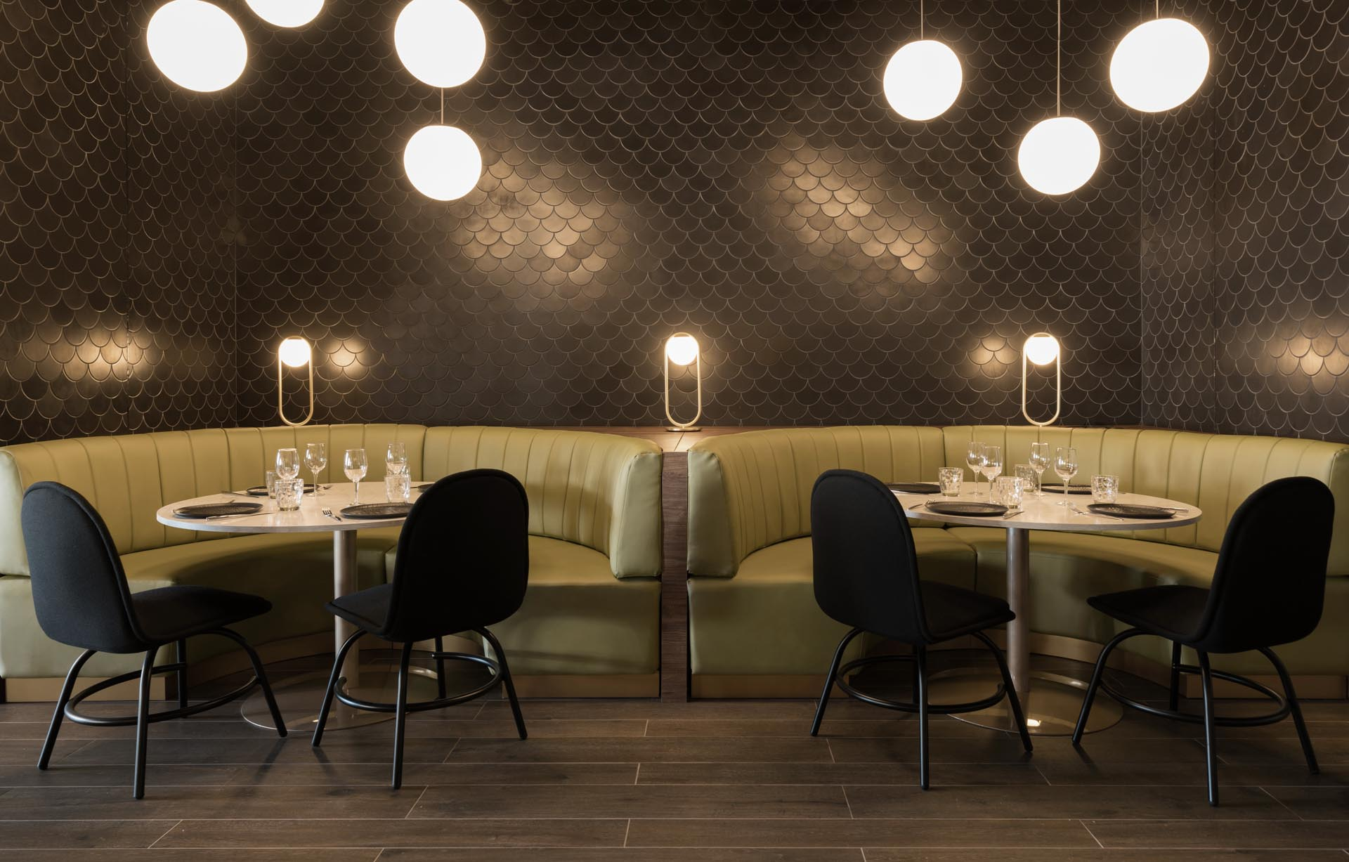 A modern restaurant with curved banquette booths, and black tiles designed to look like dragon scales.