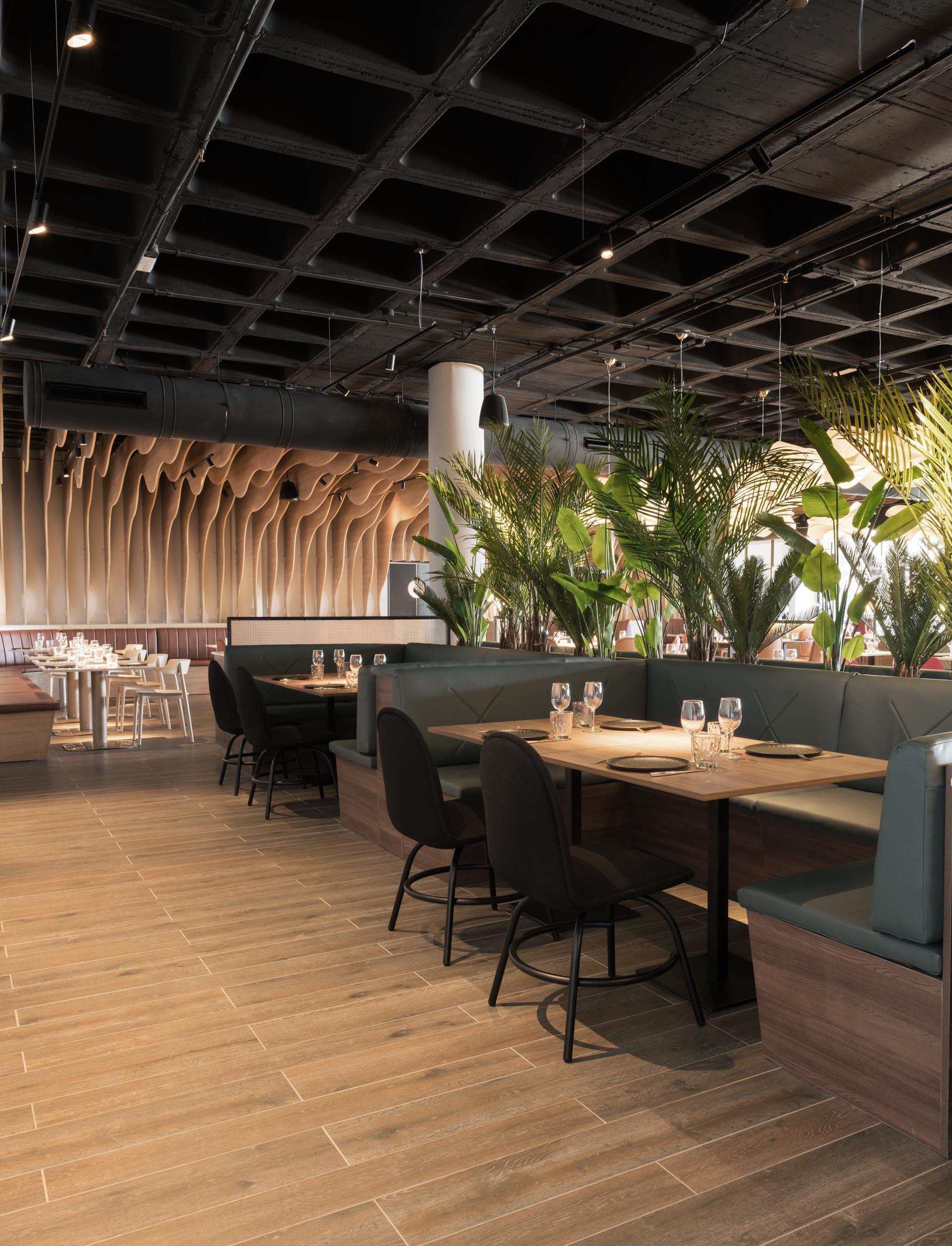 A modern restaurant with sculptural wood fins and black details.