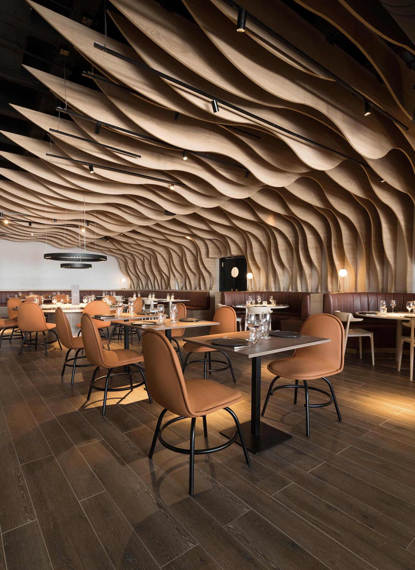 A modern restaurant with sculptural wood fins that cover the walls and ceiling, and match the surrounding furniture.