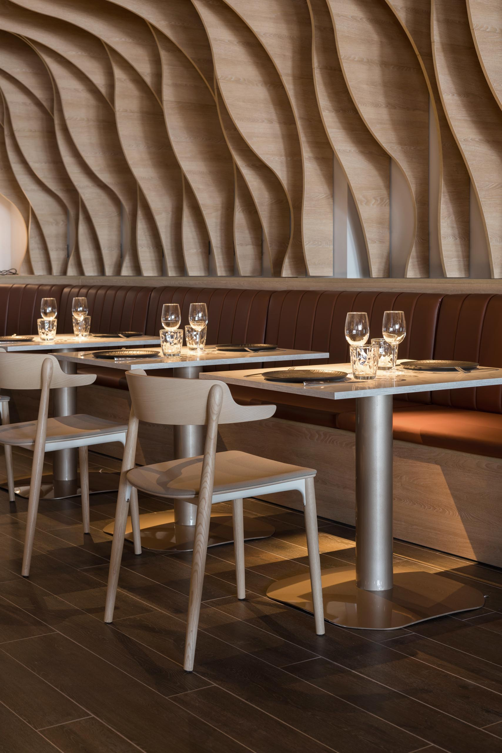 Sculptural wood fins cover the walls and ceiling, and match the surrounding furniture in a restaurant.