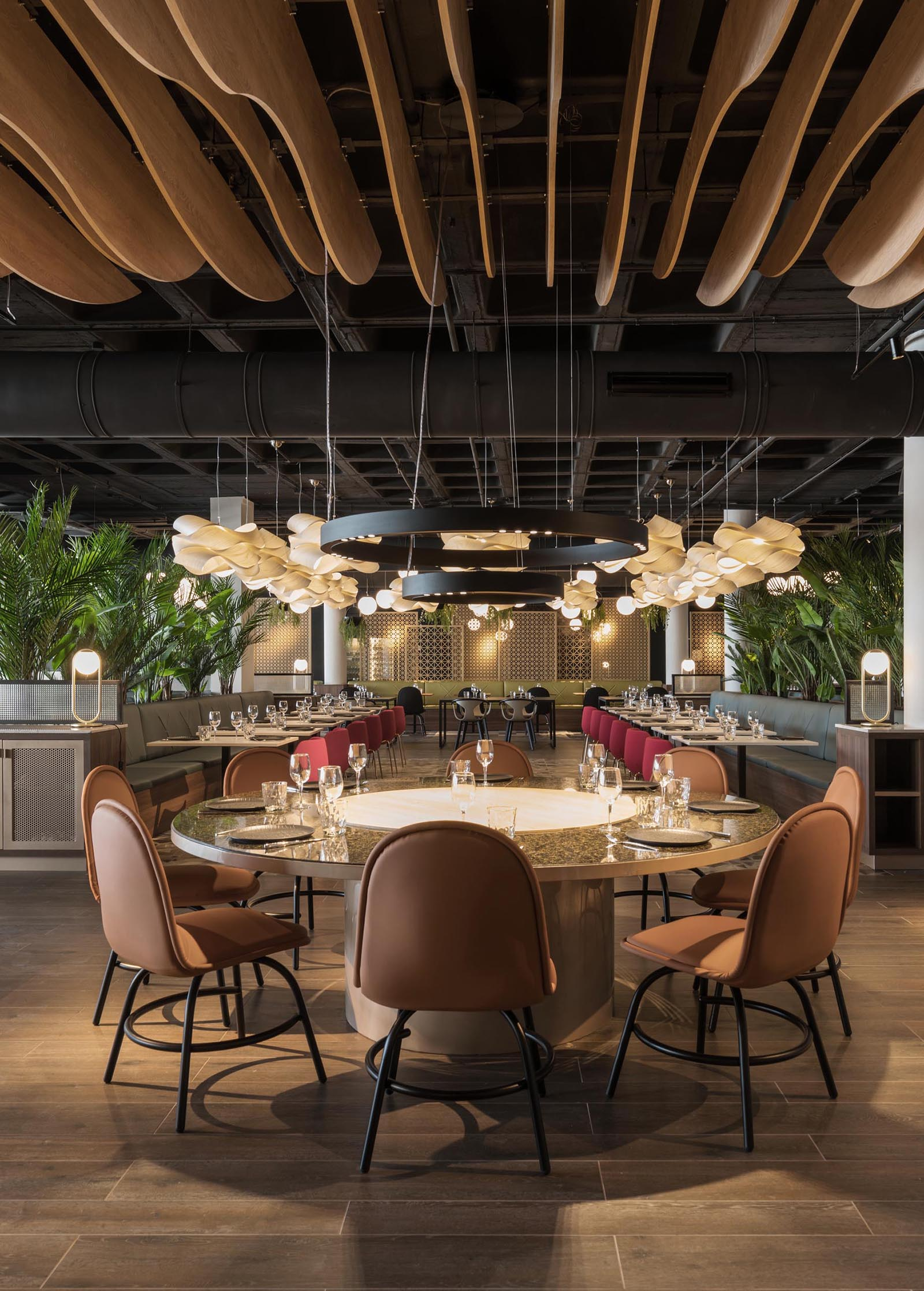 A modern restaurant with sculptural wood elements, a crown of lights, and multiple seating areas.