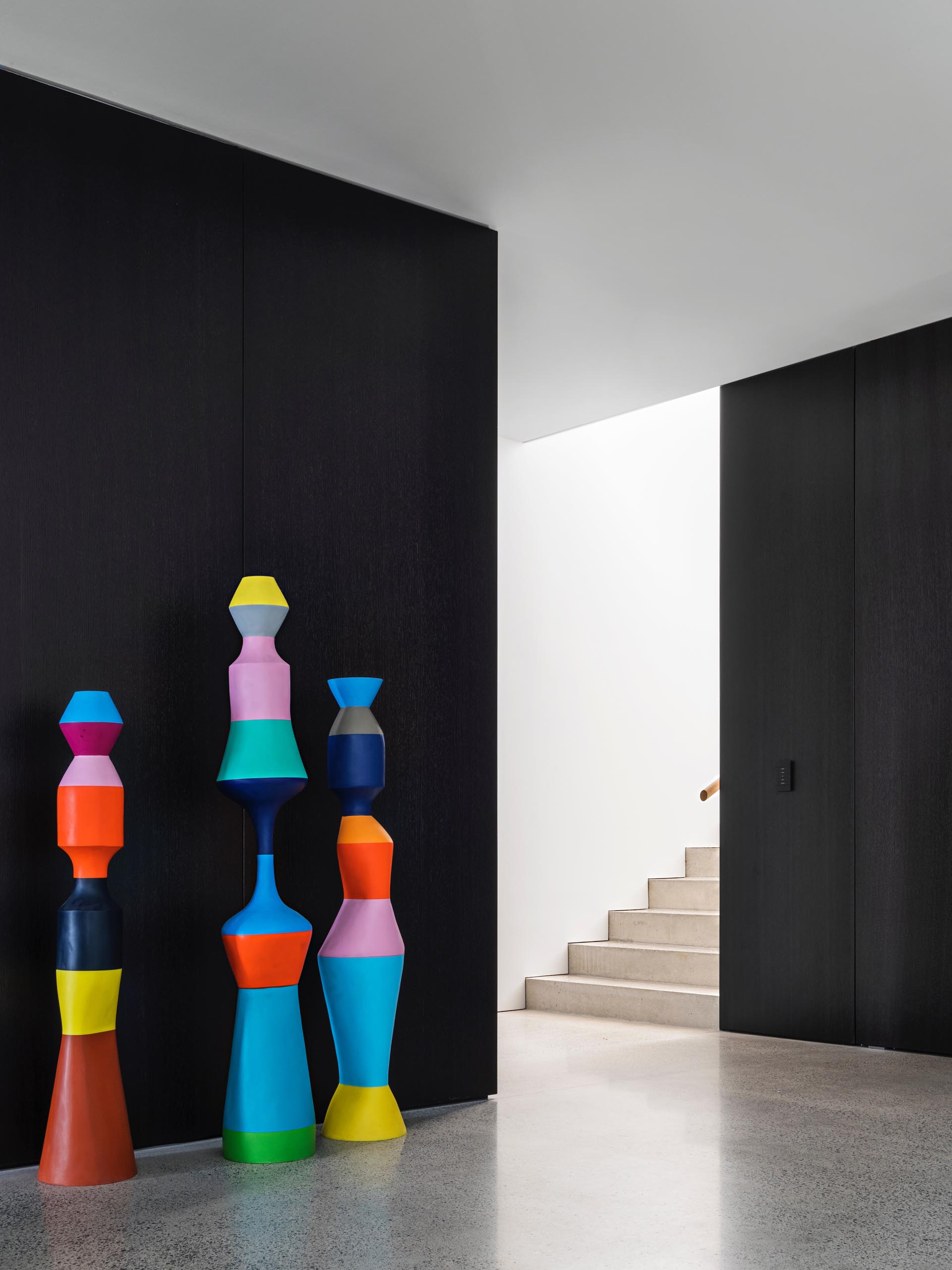 A modern interior with colorful sculptures against a black wall.