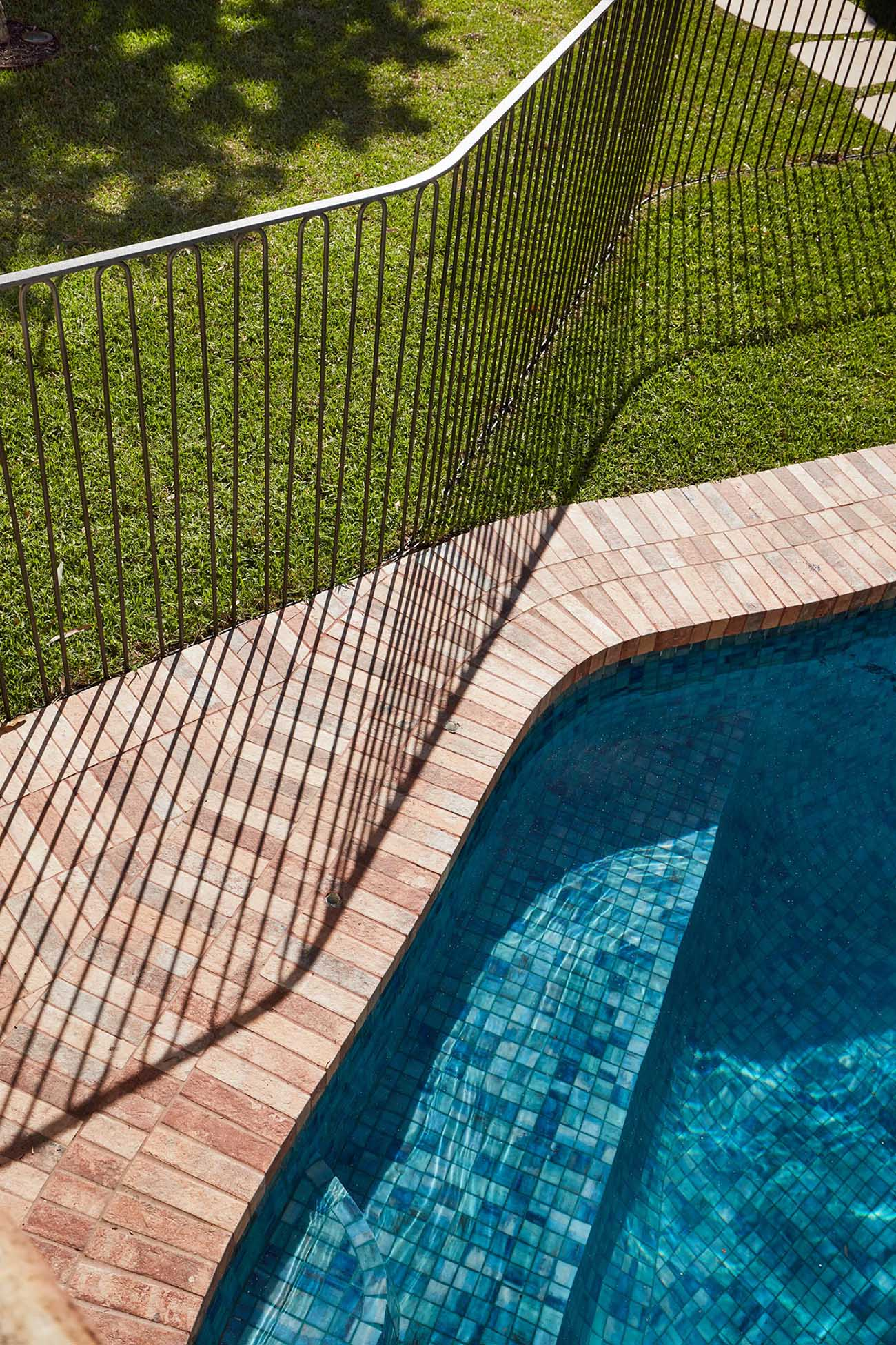 A modern safety fence surrounds a swimming pool.