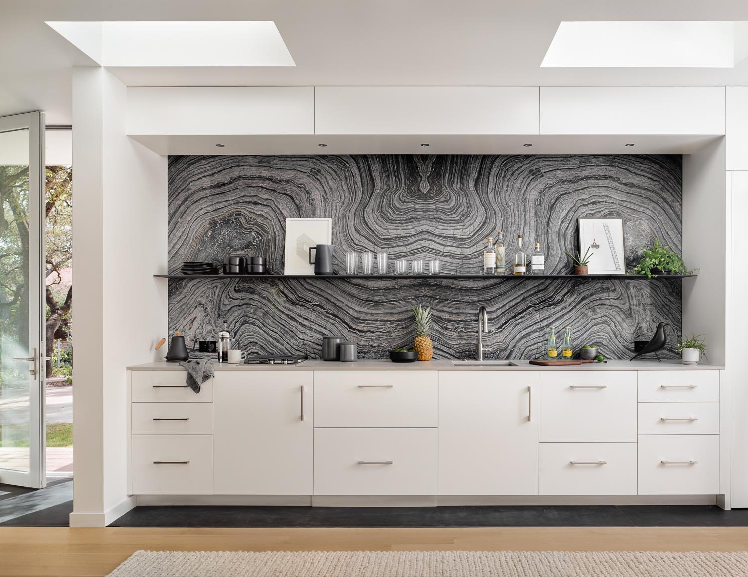 A modern small kitchen with white cabinets and a gray stone backsplash with a minimalist black shelf. Two skylights help to keep the kitchen bright.