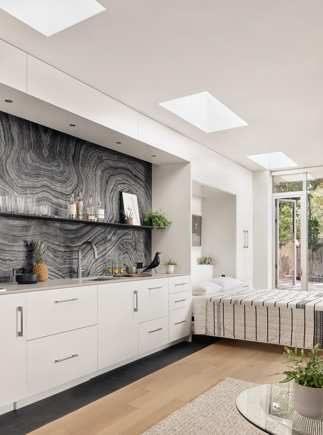 A modern accessory dwelling unit (ADU), also known as a guest house, has a fold-down murphy be next to the kitchen.