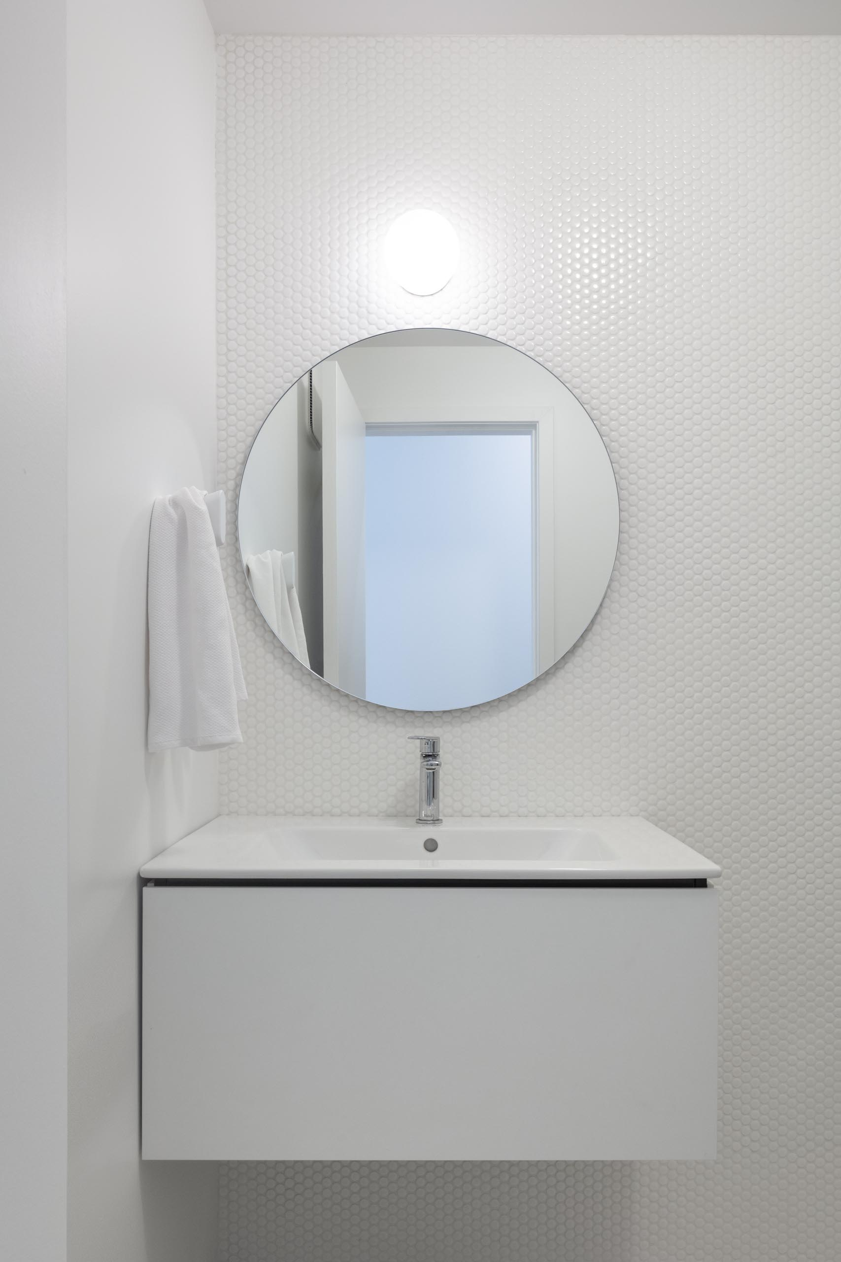 A modern white bathroom with white penny tiles and round mirror.