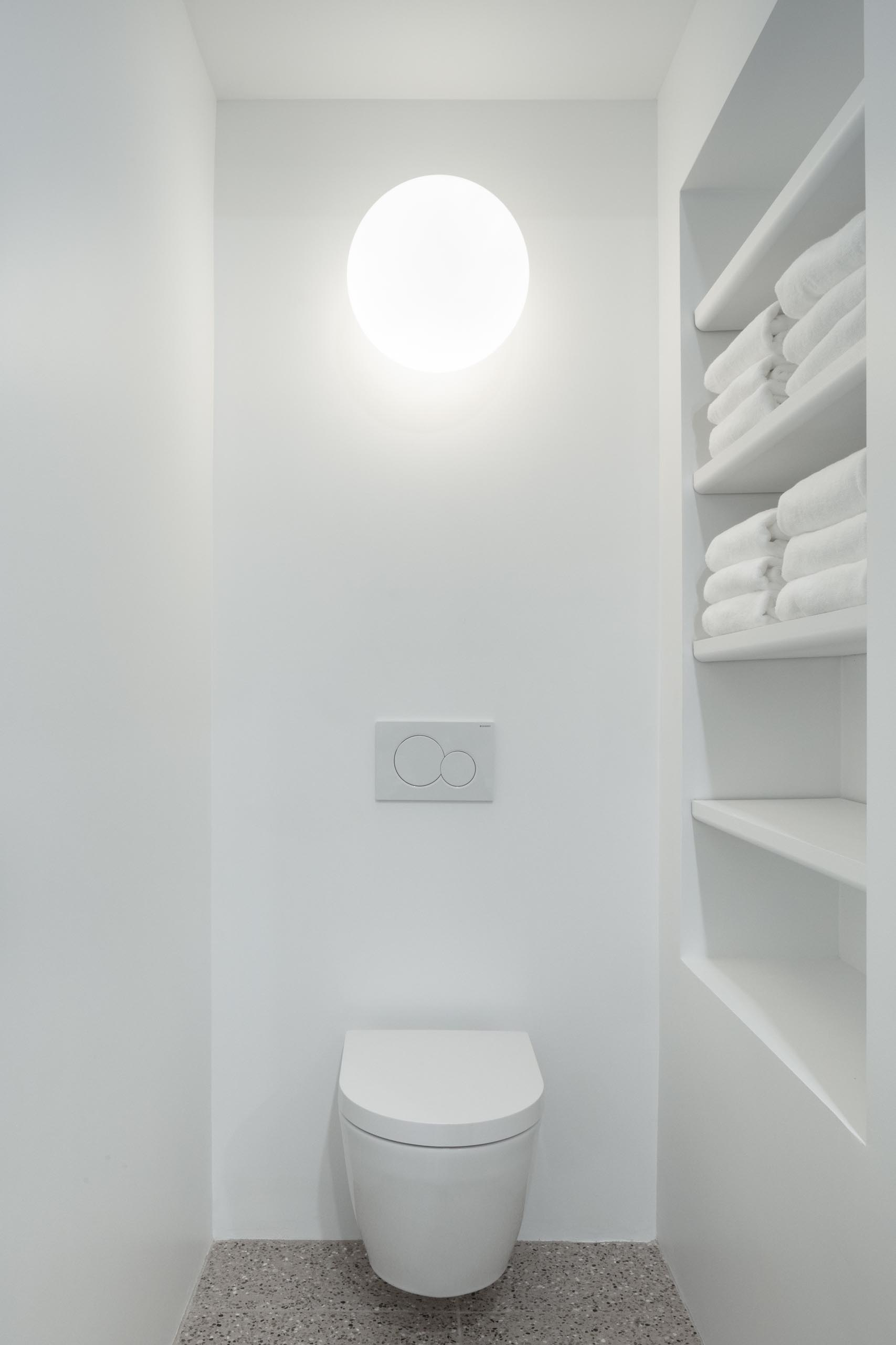 A modern white bathroom with a built-in shelving niche.