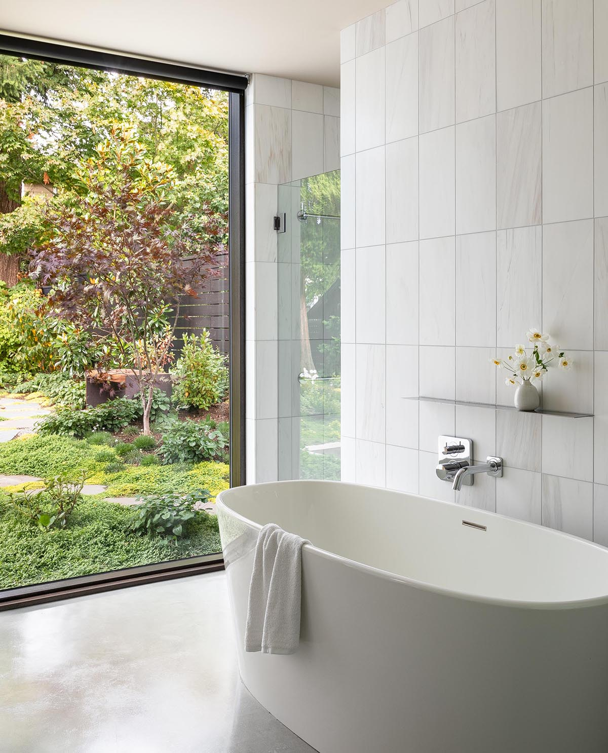 In this modern master bathroom, white tiles provide a backdrop for a freestanding bathtub and a walk-in shower.