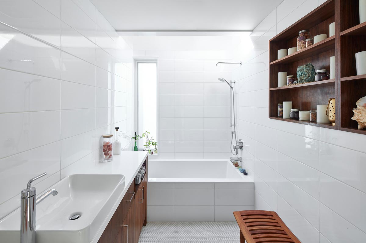 In this modern bathroom, white tiles cover the walls and the front of the built-in bathtub. Wood shelving on the wall complements the wood vanity on the opposite wall.