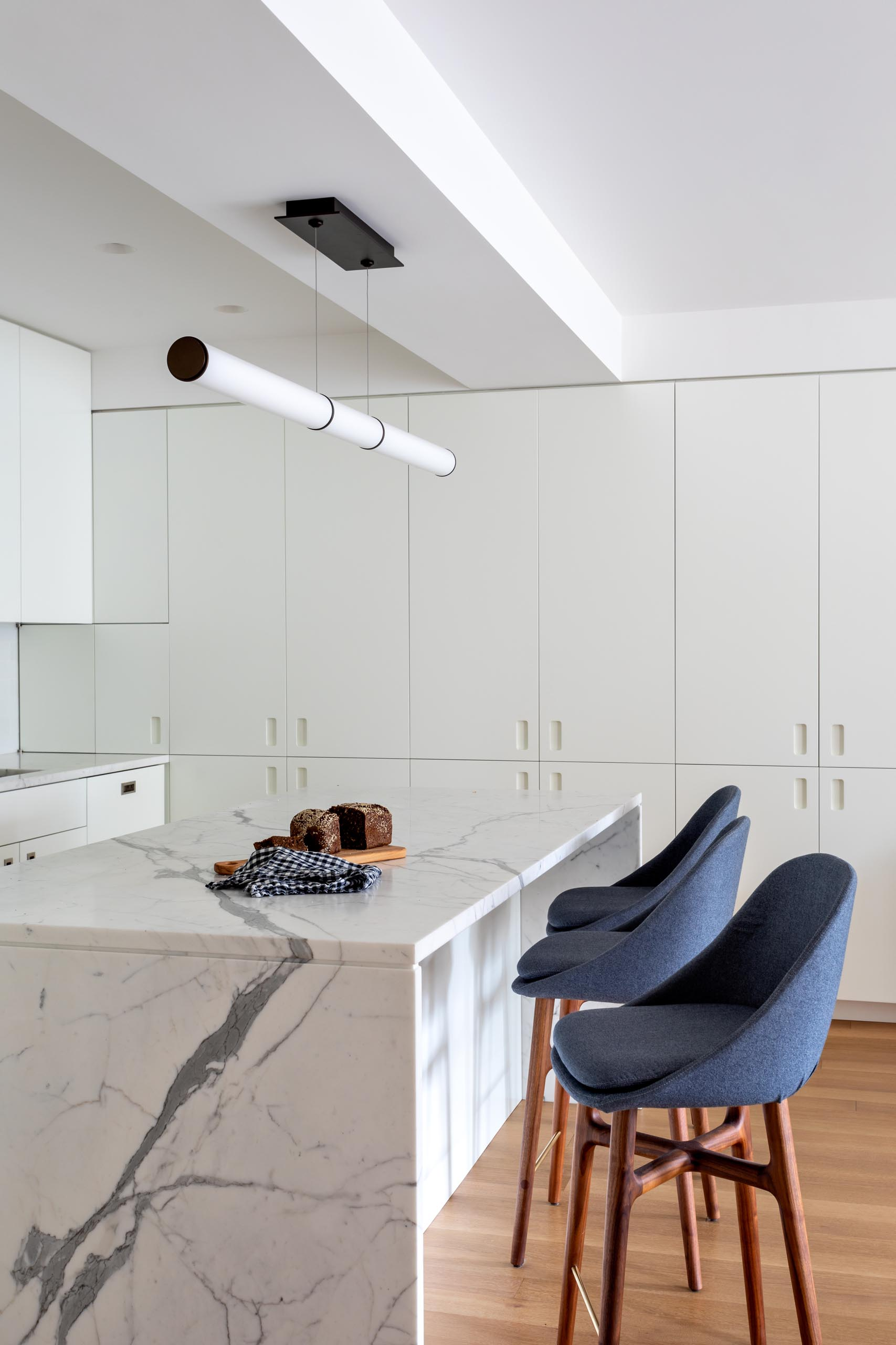 A modern kitchen has been kept bright with modern white cabinets, integrated appliances, subway tiles, and a matching island.