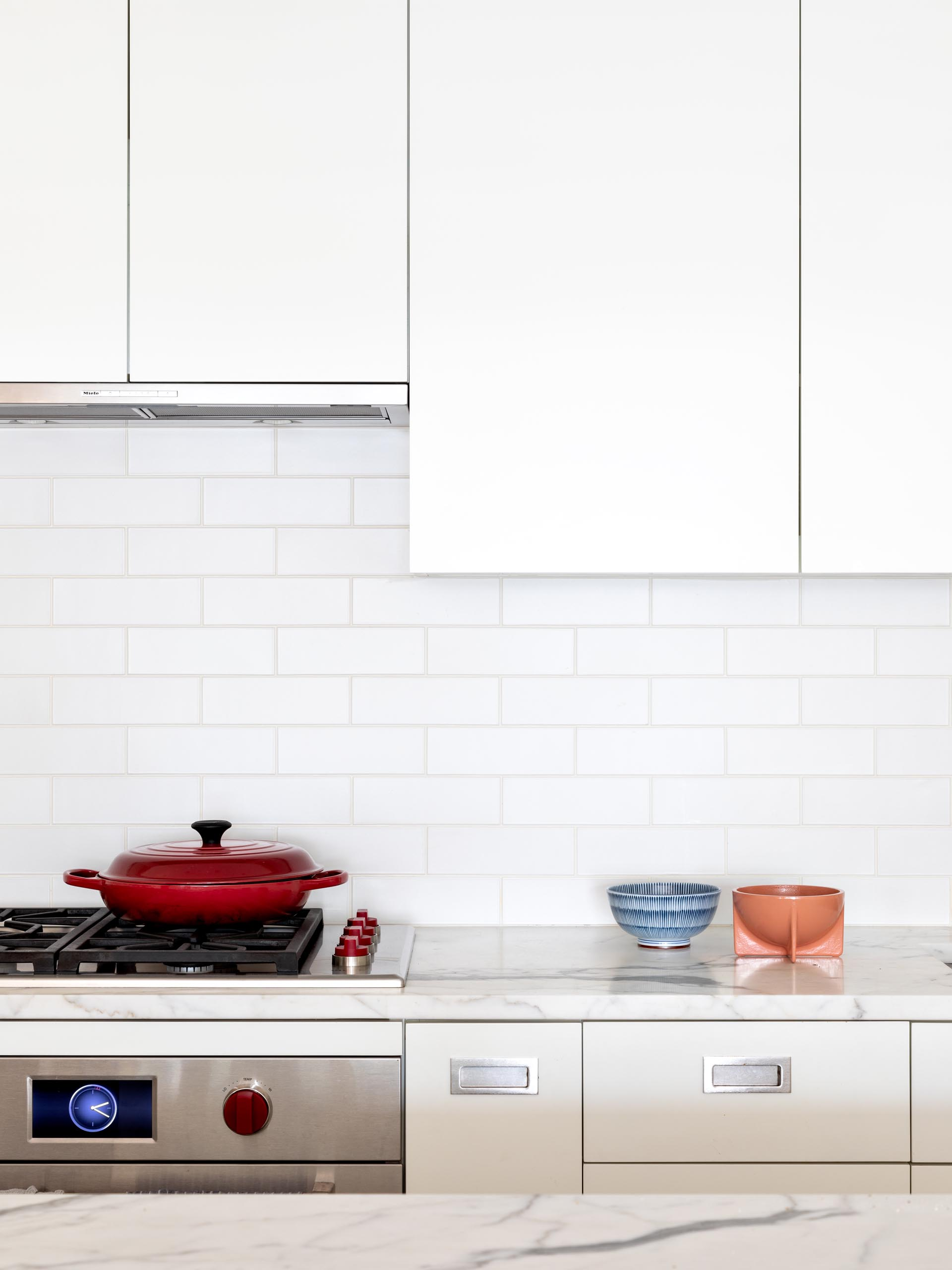 A modern kitchen has been kept bright with modern white cabinets, integrated appliances, and subway tiles, and a matching island.