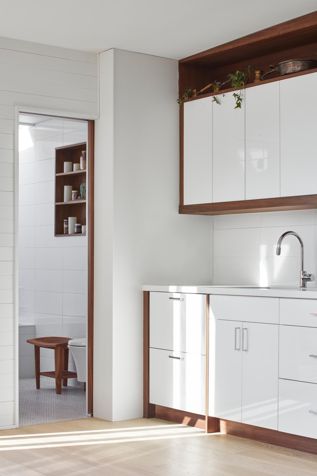A small kitchenette with white and wood cabinetry and a matching white countertop.