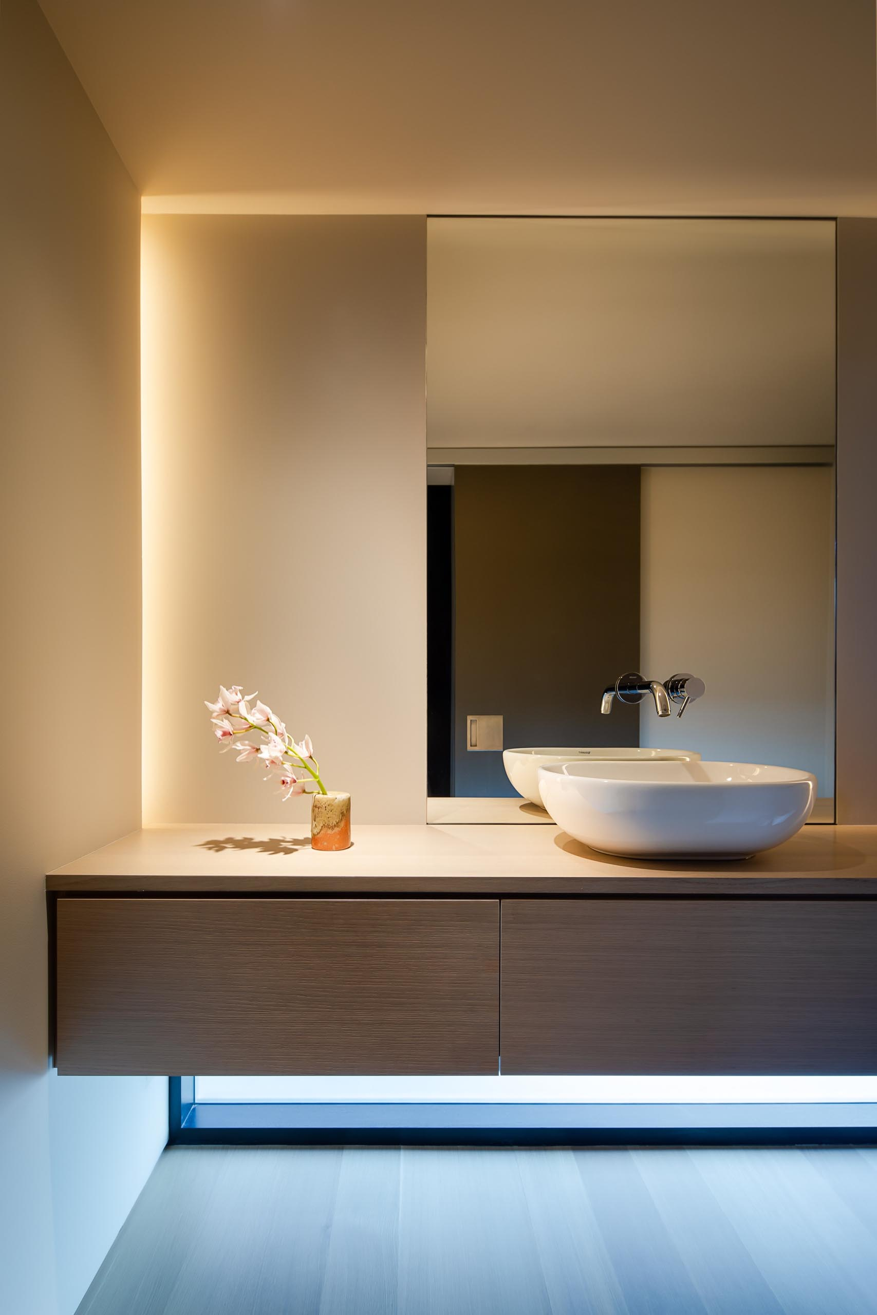In this modern bathroom, there's a floating wood vanity with hidden lighting tucked away in the corner.