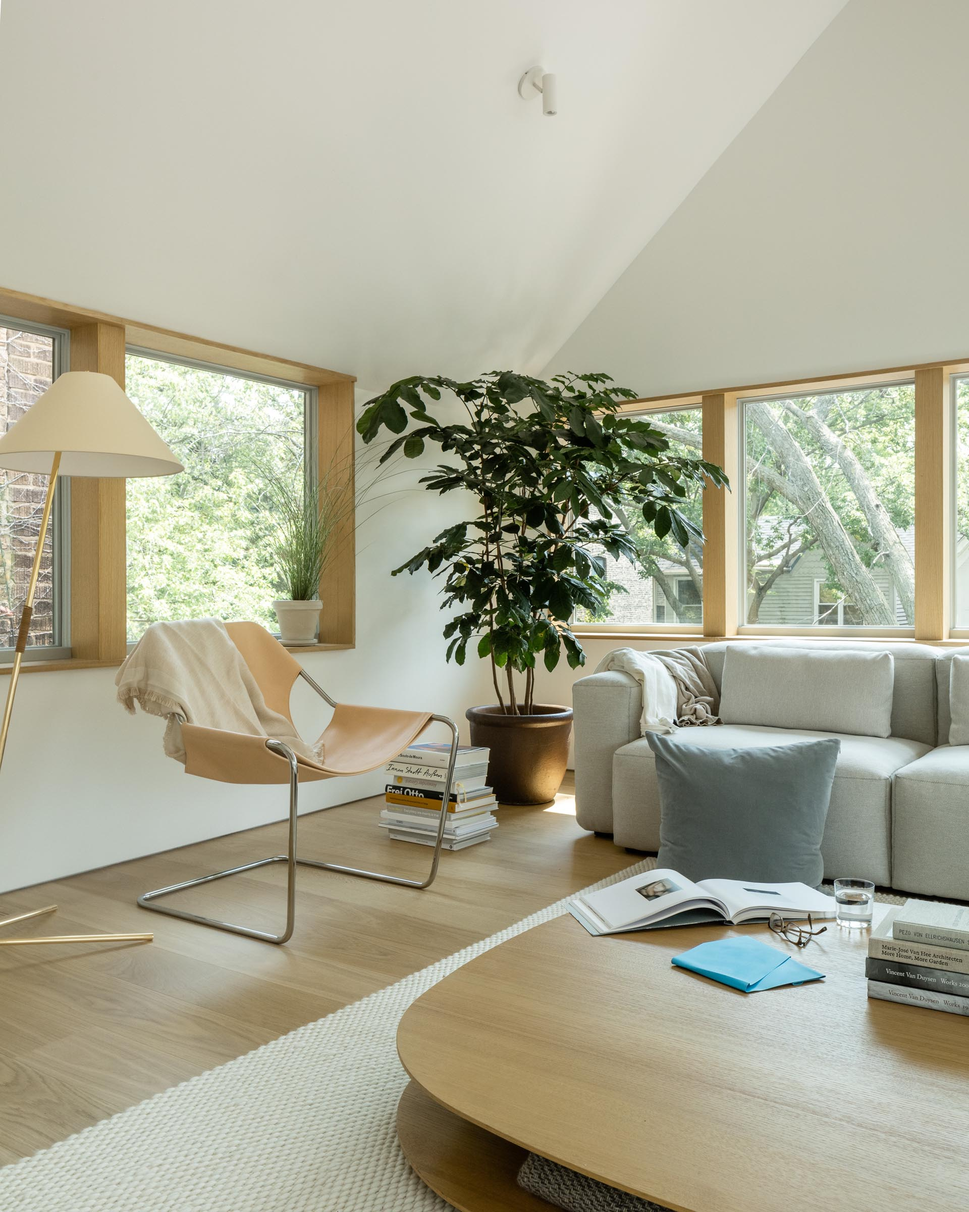 This modern living room has a vaulted ceiling, wood window frames, and minimalist furnishings.