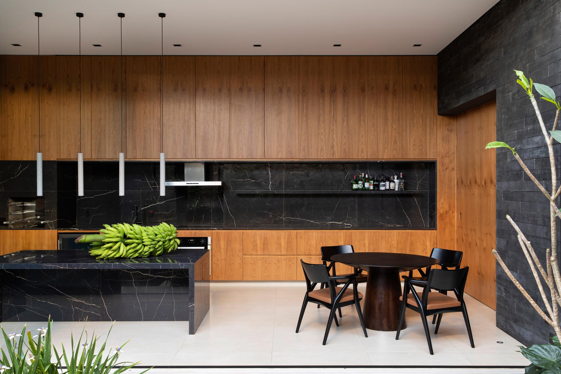 In this modern kitchen, the wood cabinets are contrasted by black stone that used for the backsplash, floating shelf, and island.