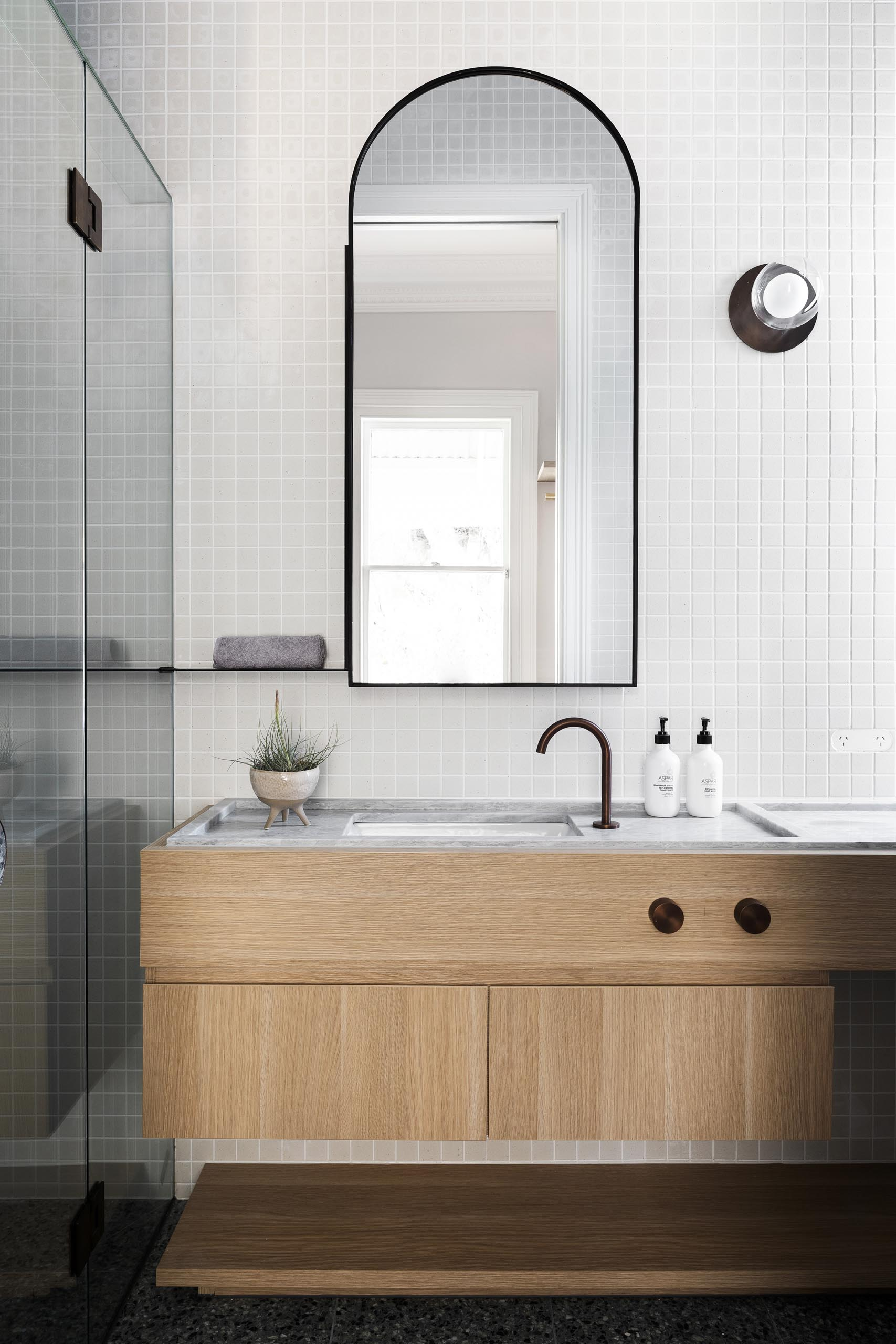 A modern bathroom with a wood vanity, tiled wall, and an arched mirror.