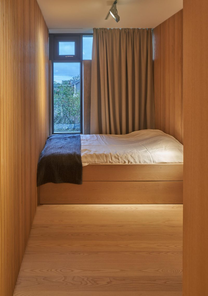 A modern bedroom lined with wood that has a built-in bed.