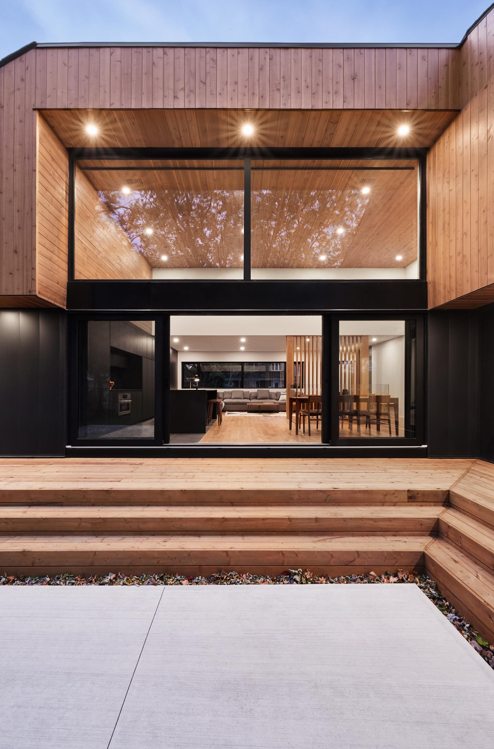 A modern home with high ceilings, and a black framed sliding lass door.