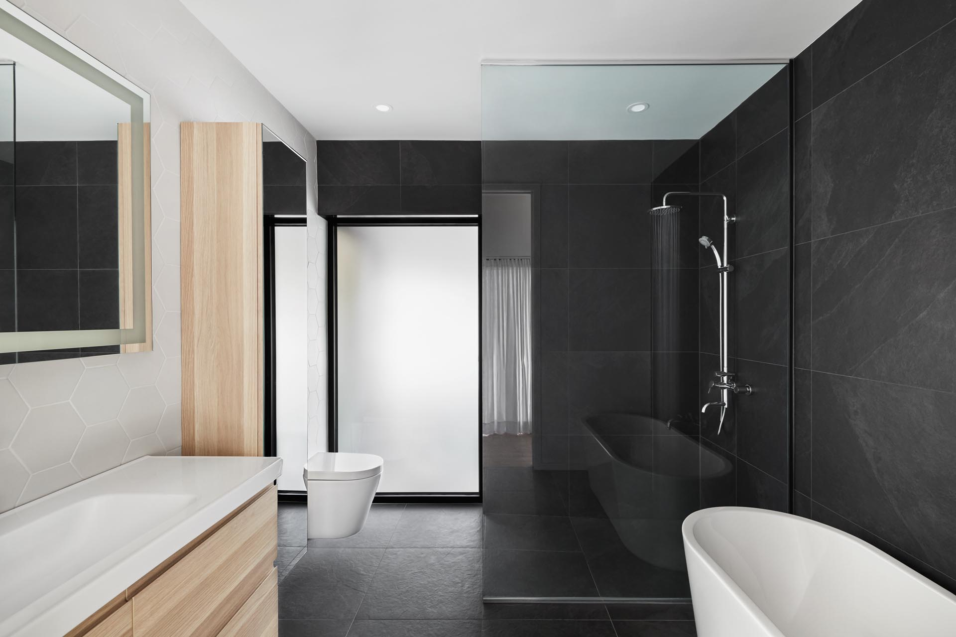 In this modern bathroom, large format black tiles cover two of the walls, while there's a light wood vanity, and a wall of white hexagonal tiles.
